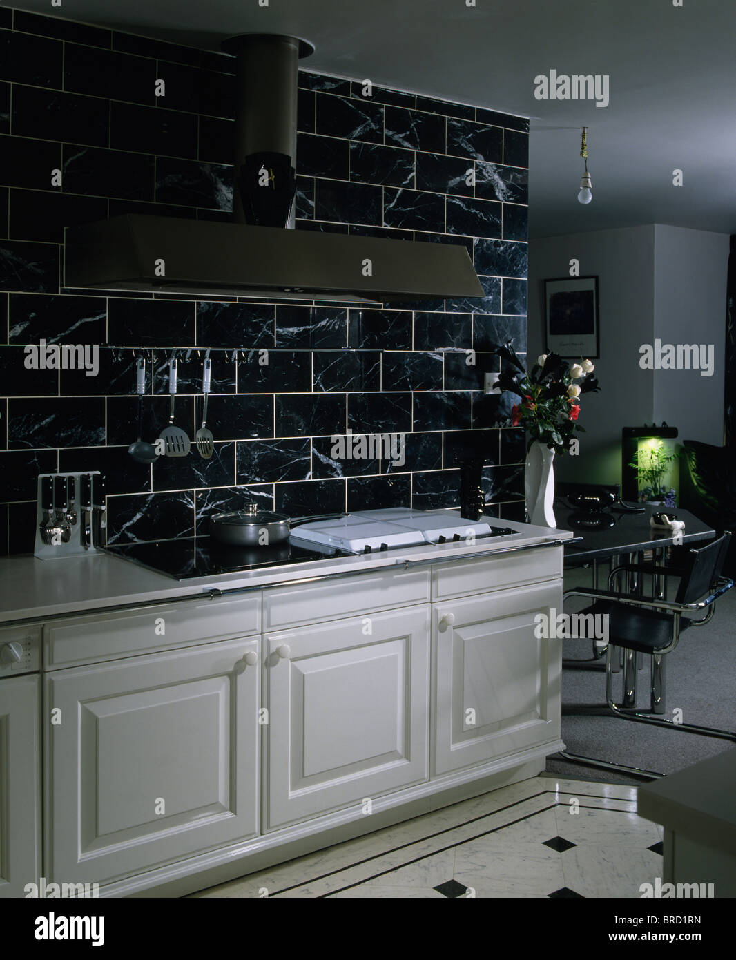Black wall tiles above white fitted units in modern white kitchen ...