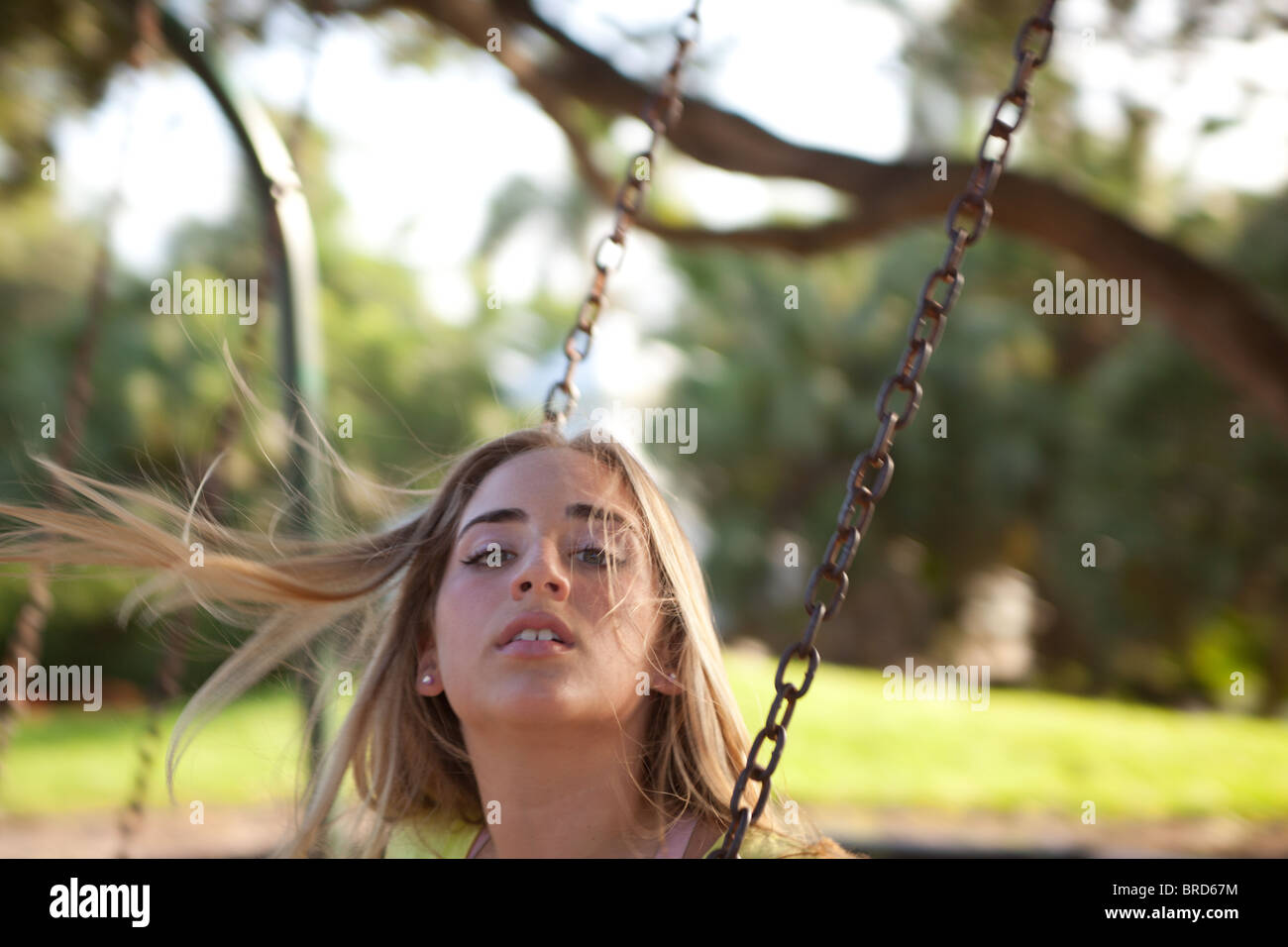 Young girl in her teens looks up from a swing at the park, her hair