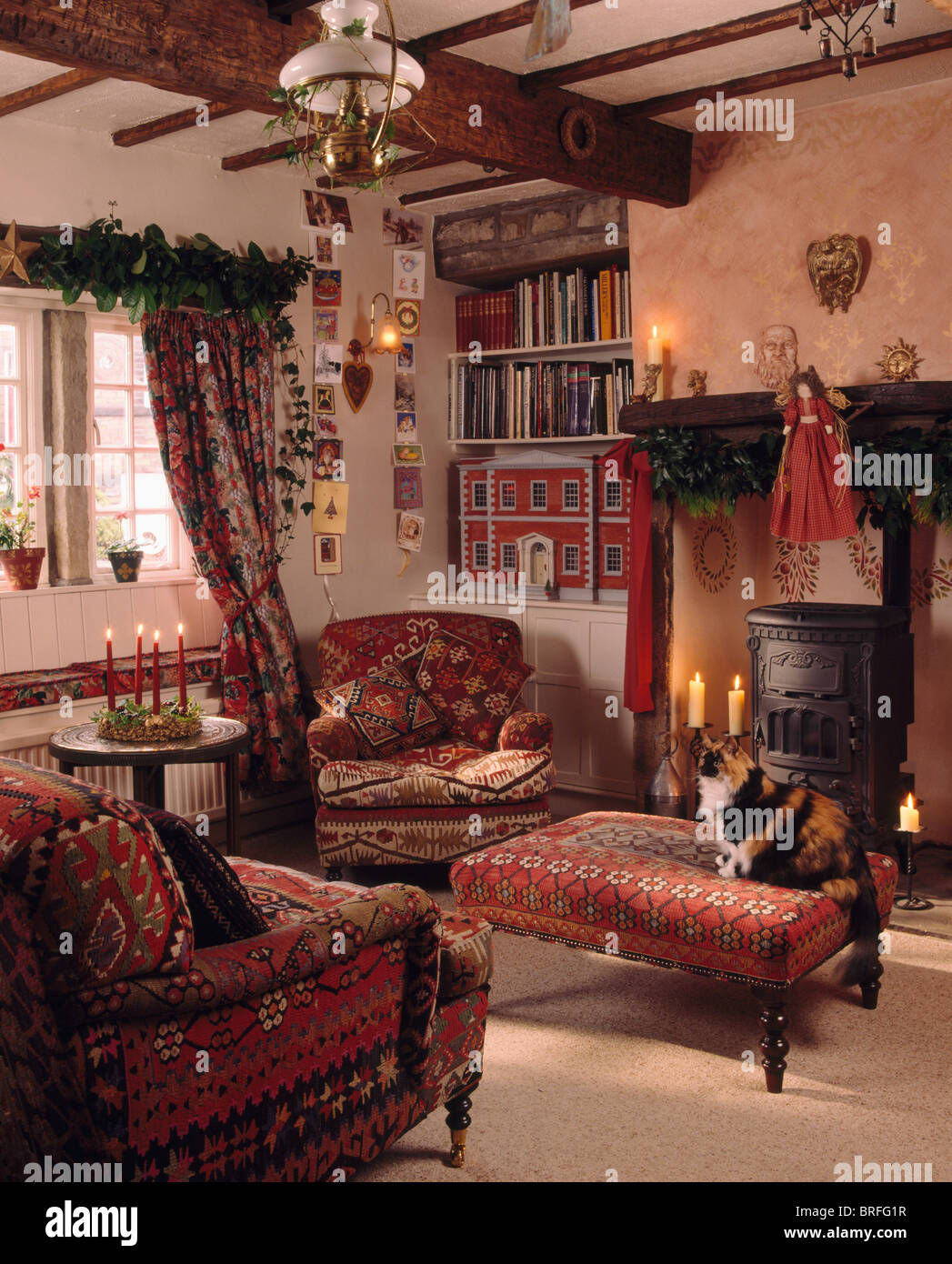 upholstered stools for living room. Cat sitting on red upholstered stool in cottage living room decorated for  Christmas with foliage and lighted candles