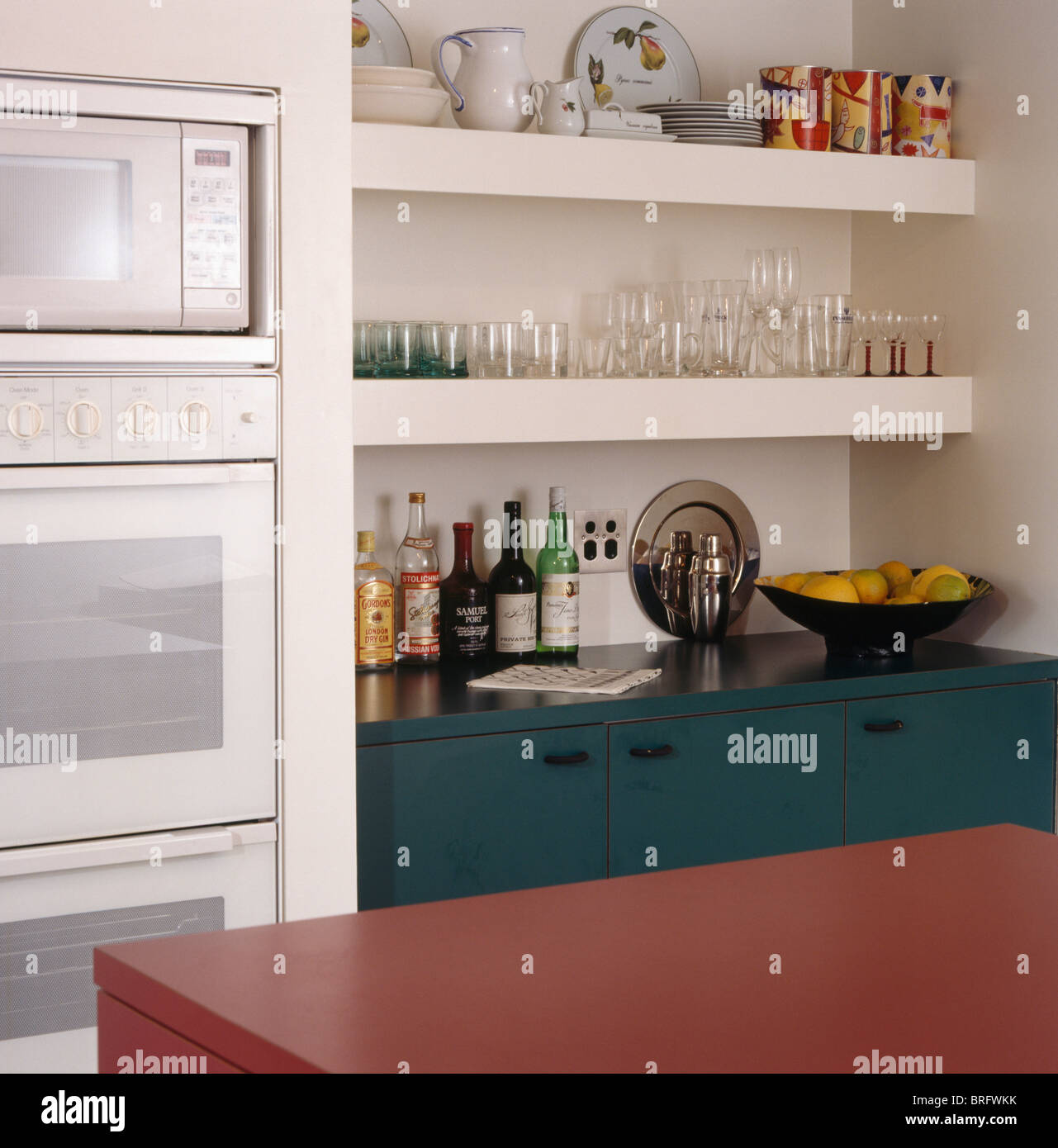 Close-up of microwave and oven in fitted unit beside glasses and ...