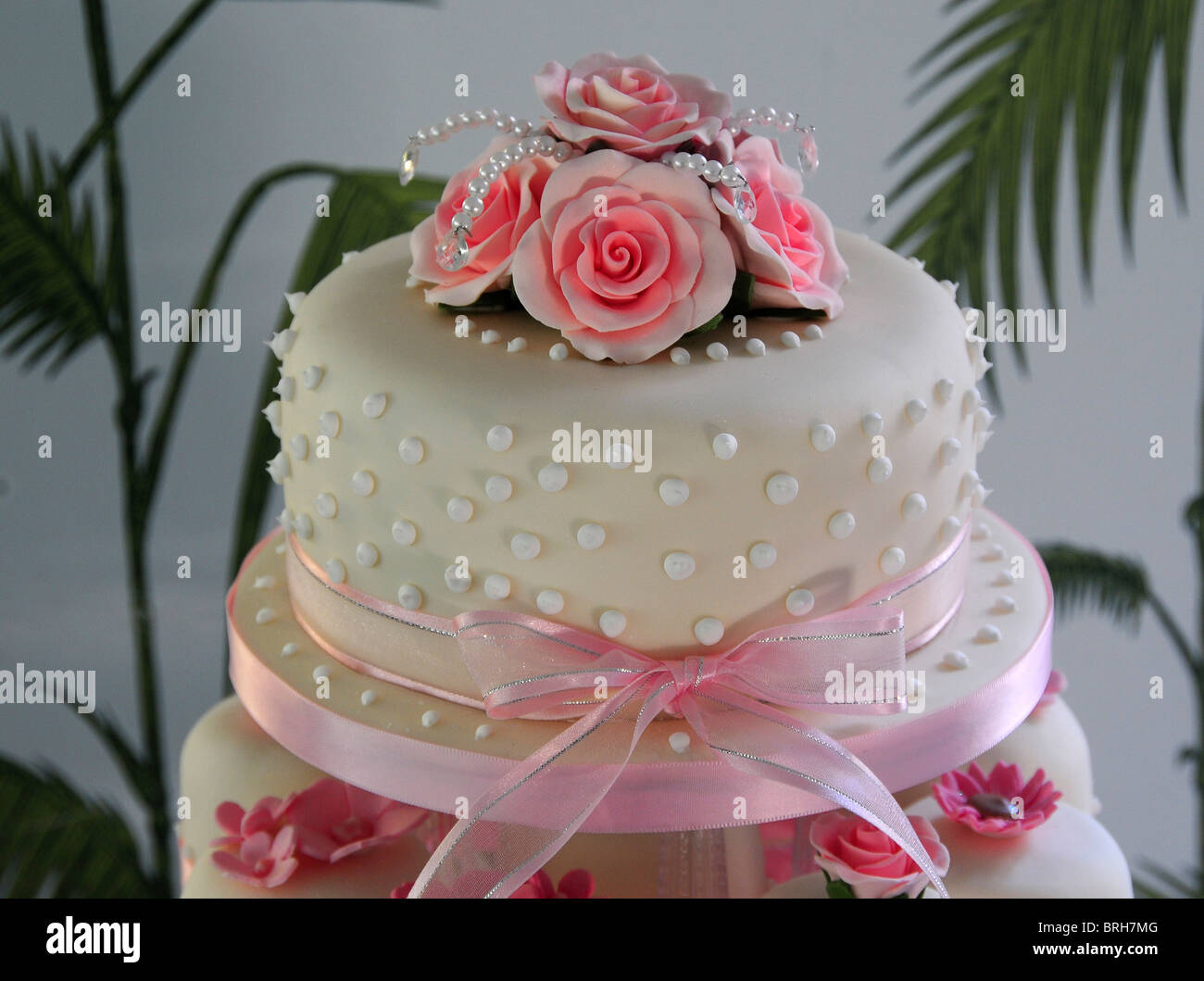 The top tier of a pink and white wedding cake made up with cup ...