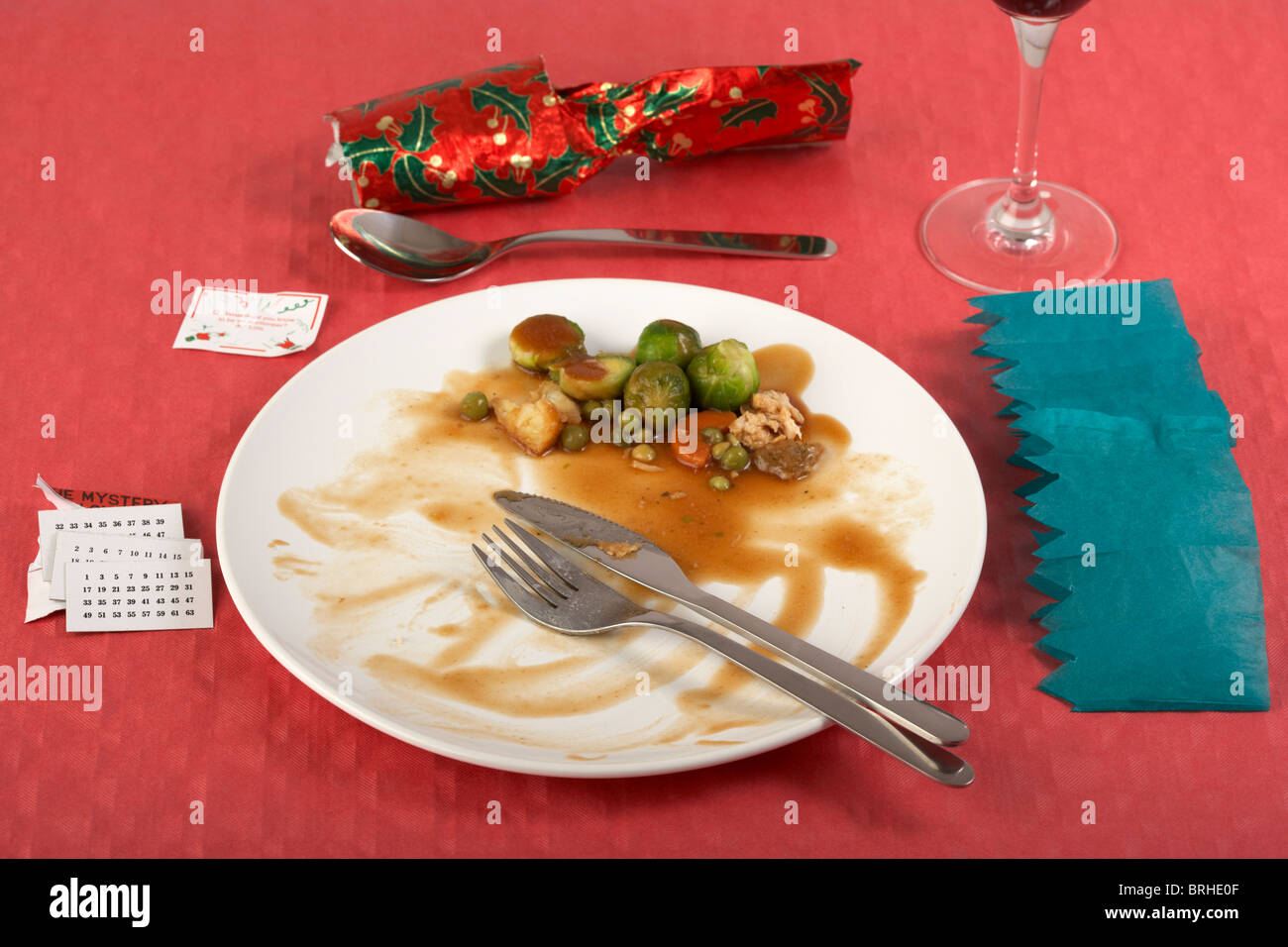 finished christmas dinner with sprouts left on white dinner plate on red tablecloth christmas cracker opened & finished christmas dinner with sprouts left on white dinner plate on ...