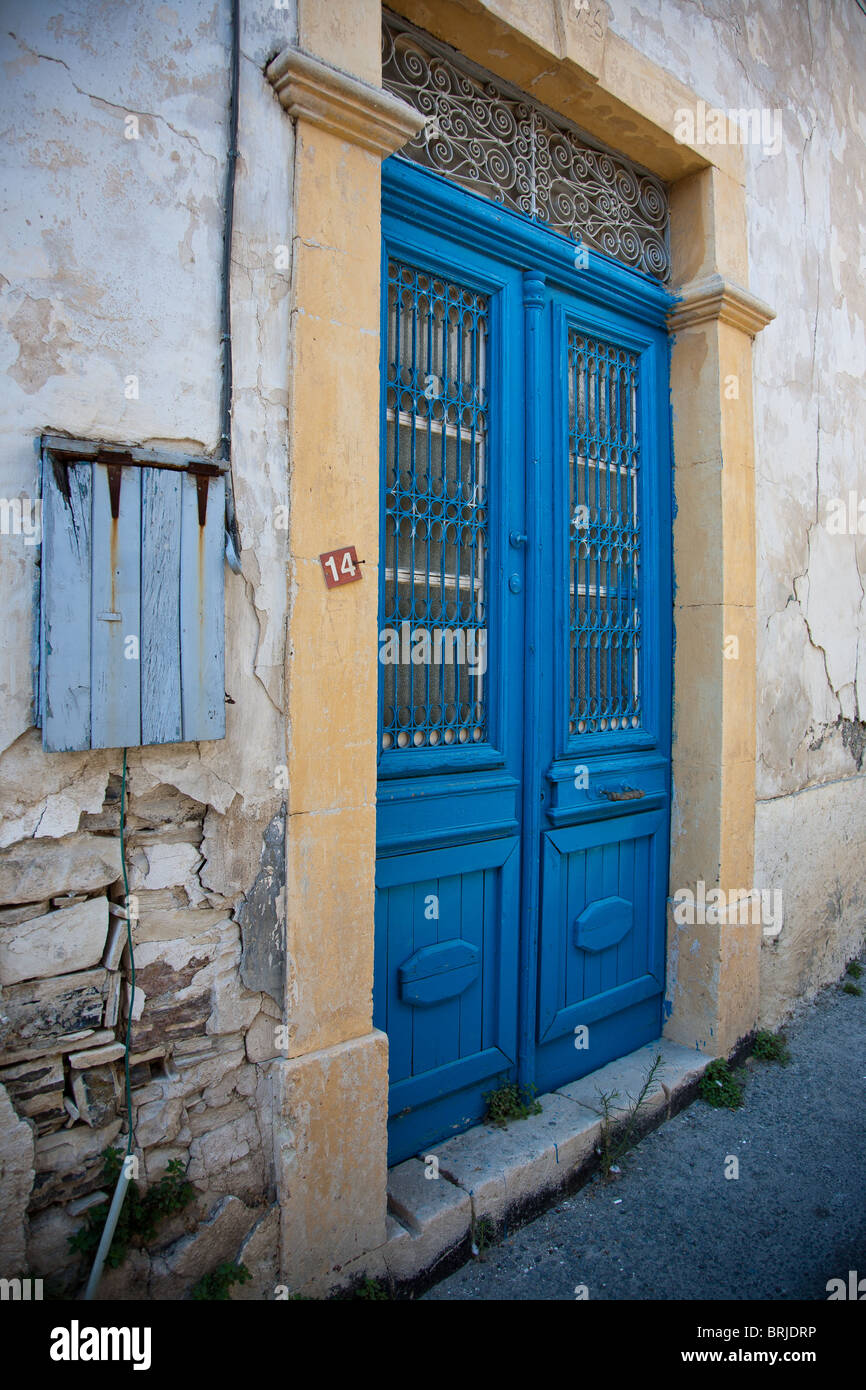 A blue door at number 14 in the village of lefkara known for 14 door
