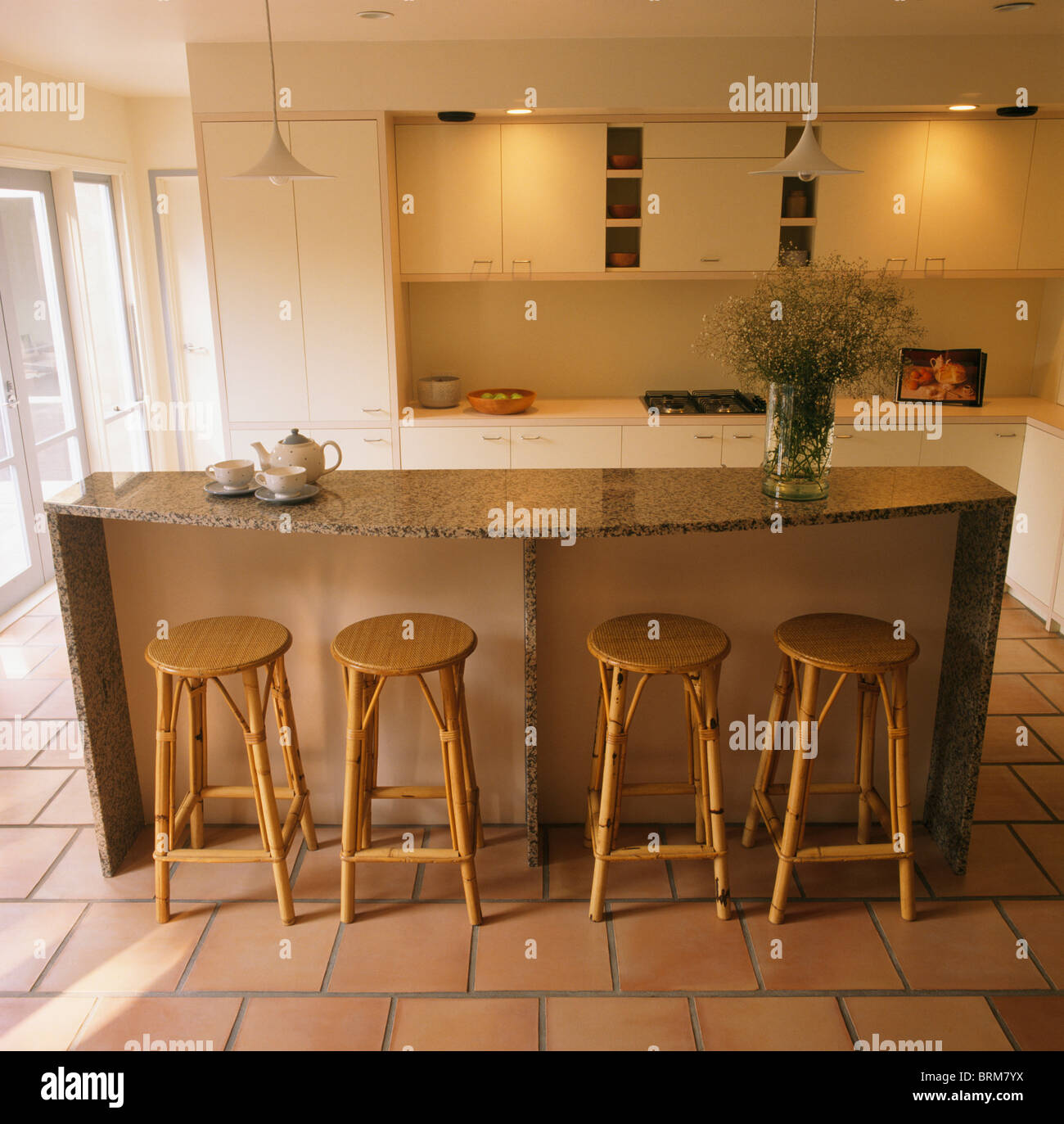 Cane Stools At Breakfast Bar On Granite Topped Island Unit