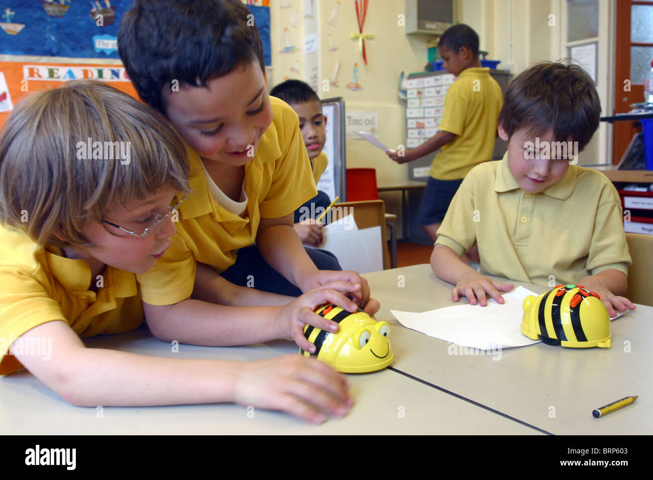 Primary School Children In Classroom Playing With Wind Up Bumble Bee Toys