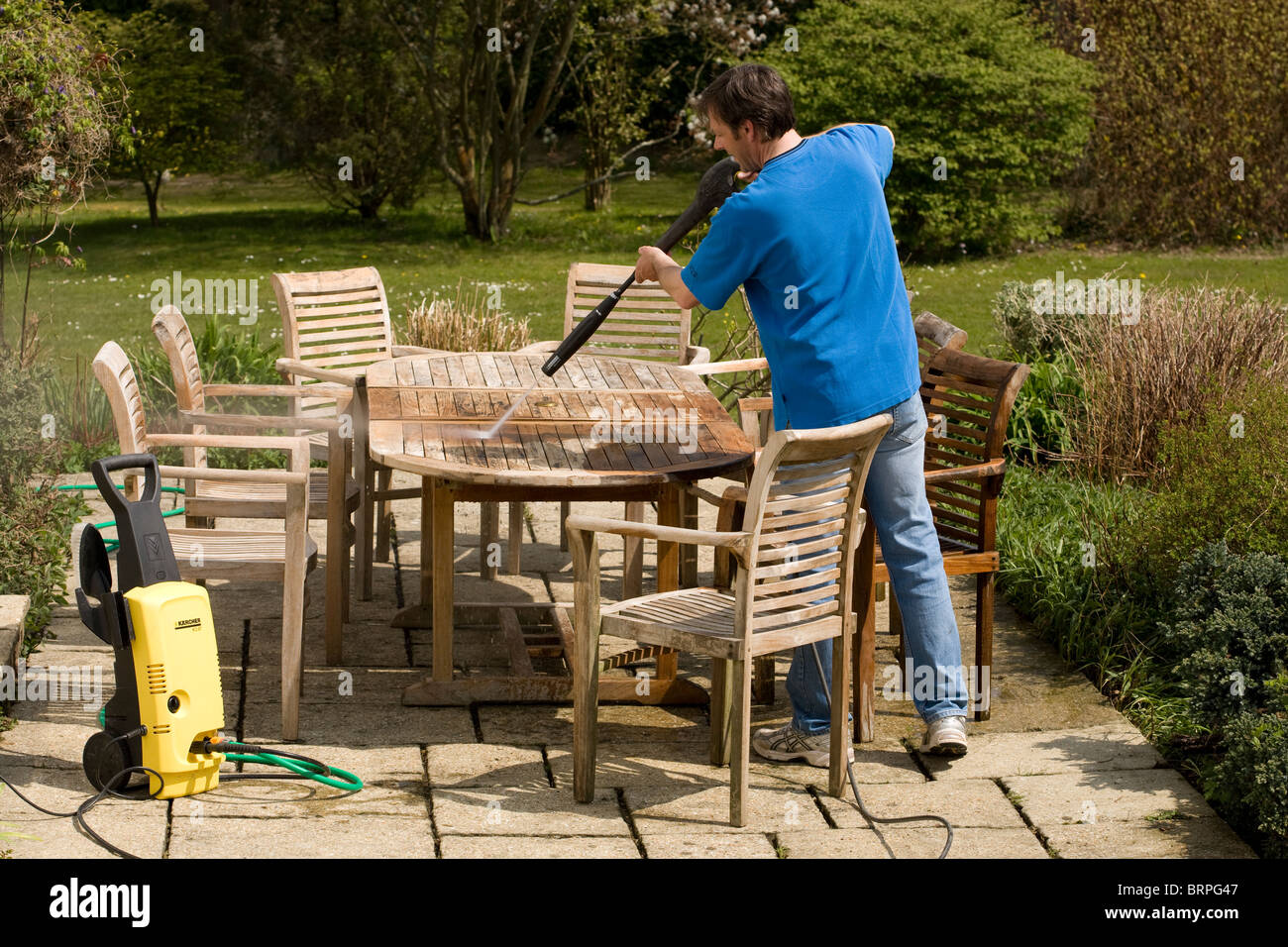 Man using a pressure washer to clean teak wood garden furniture. Man using a pressure washer to clean teak wood garden furniture
