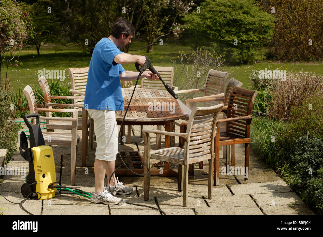 Man Using A Pressure Washer To Clean Teak Wood Garden Furniture. Man Using  A Pressure Part 61
