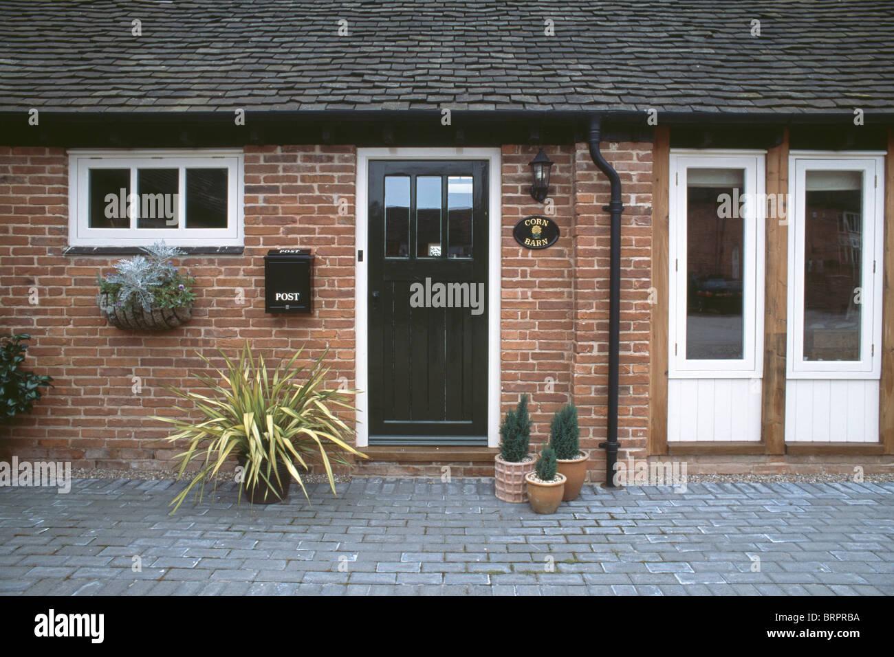 Plants in pots beside black front door beside french doors on plants in pots beside black front door beside french doors on traditional single story house rubansaba