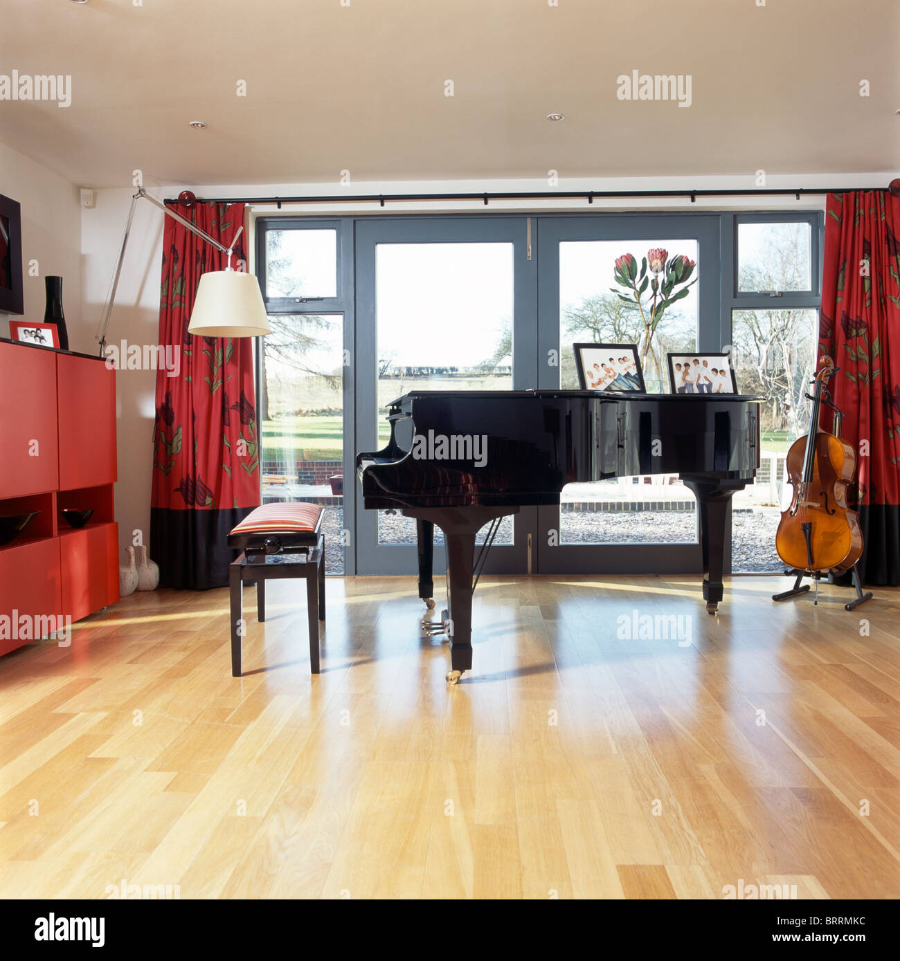Empty room with chair violin and sheet music on floor photograph - Grand Piano In Front Of French Windows In Modern Music Room With Pale Wood Flooring