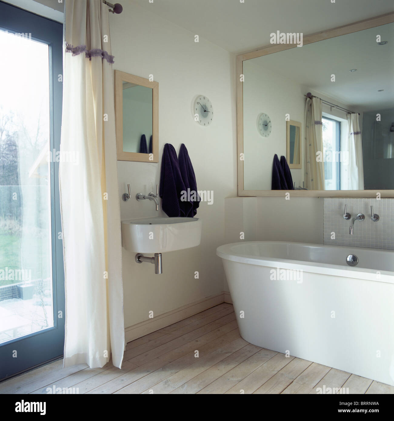 Large Mirror Above Modern Bath In Small Bathroom With Wall Mounted Basin Beside Glass Door White Curtain