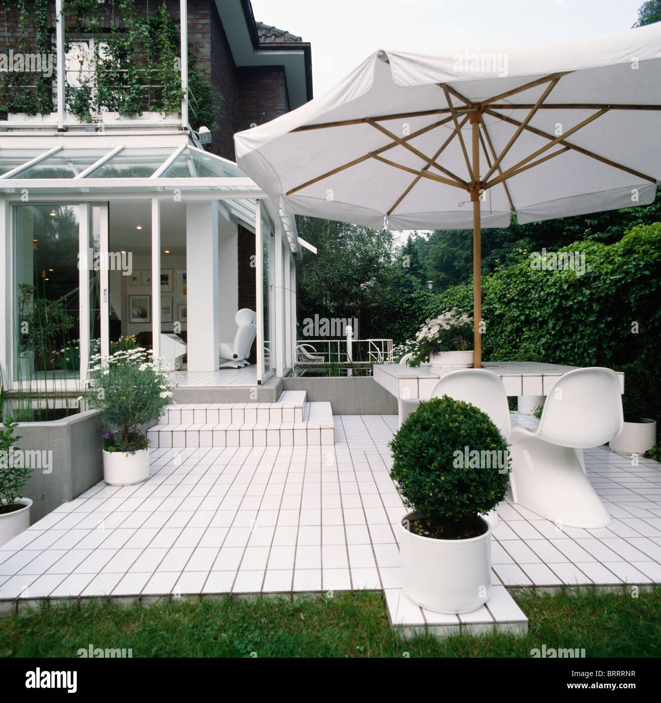 Large White Umbrella Above White Chairs And Table On White Tiled Patio With  Clipped Box In