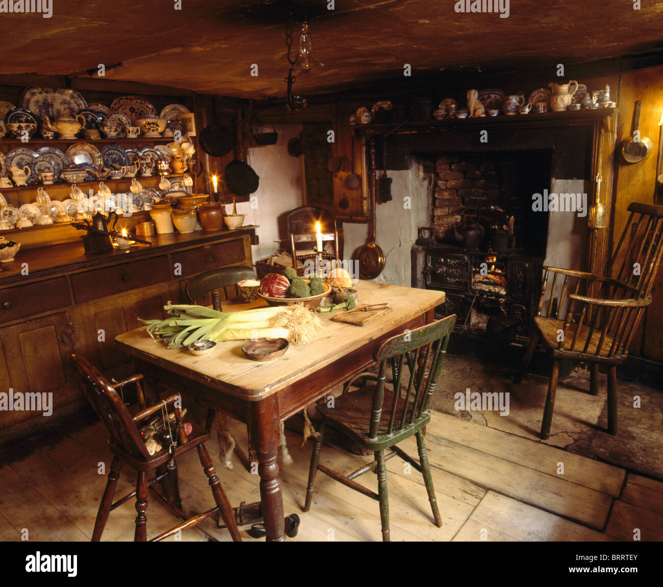 Old Pine Table And Dresser In Fashioned Kitchen Dining Room With Antique Windsor Chair Beside Fireplace Lighted Fire