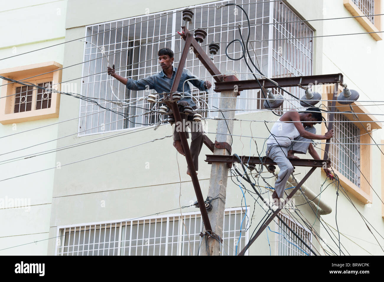 Indian Electrician Working Up An Electricity Pylon In The Streets Of Stock Photo  Royalty Free