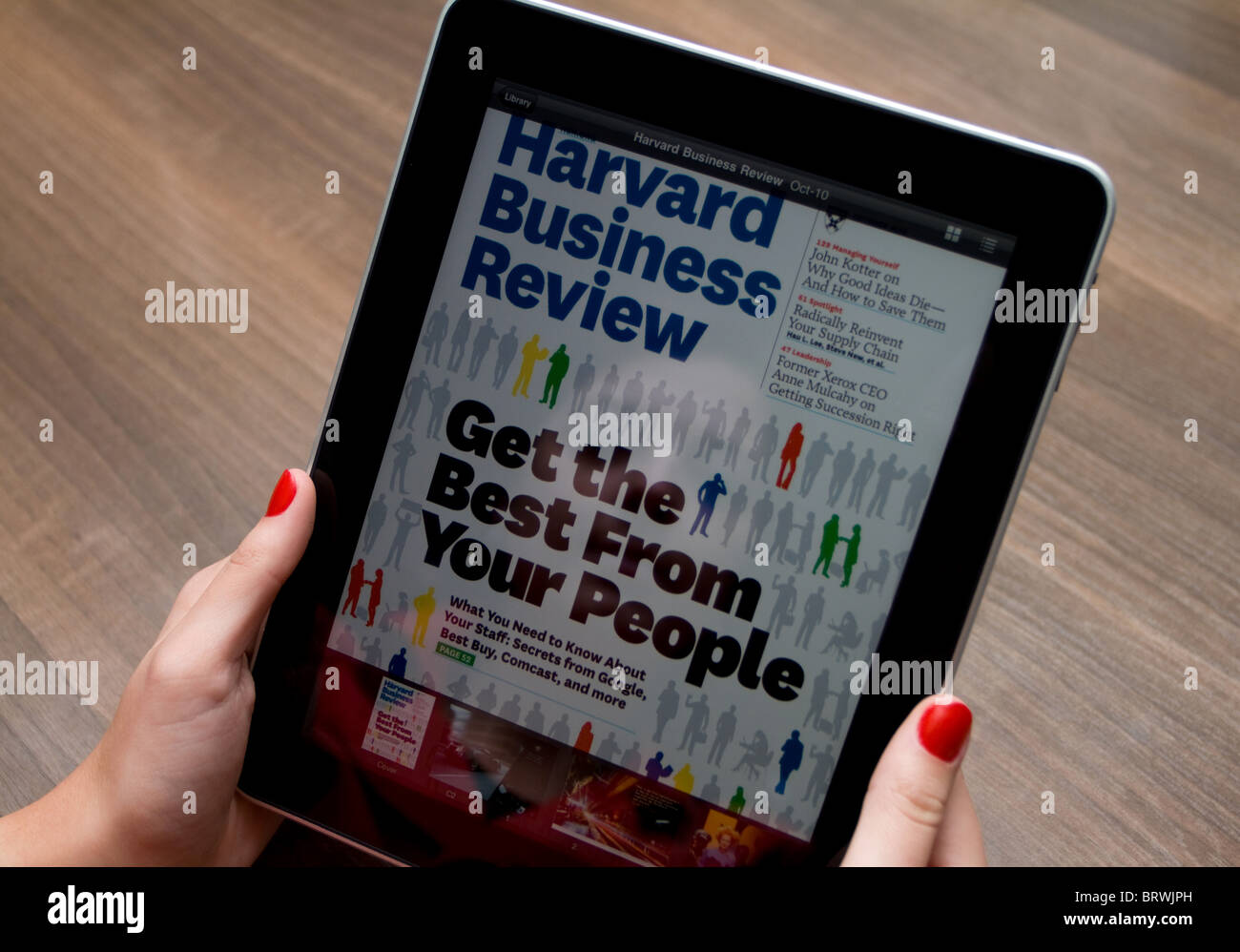 Stock Photo  Woman's Hands Holding An Apple Ipad With Her Reflection On  The Screen, Showing Harvard Business Review Magazine