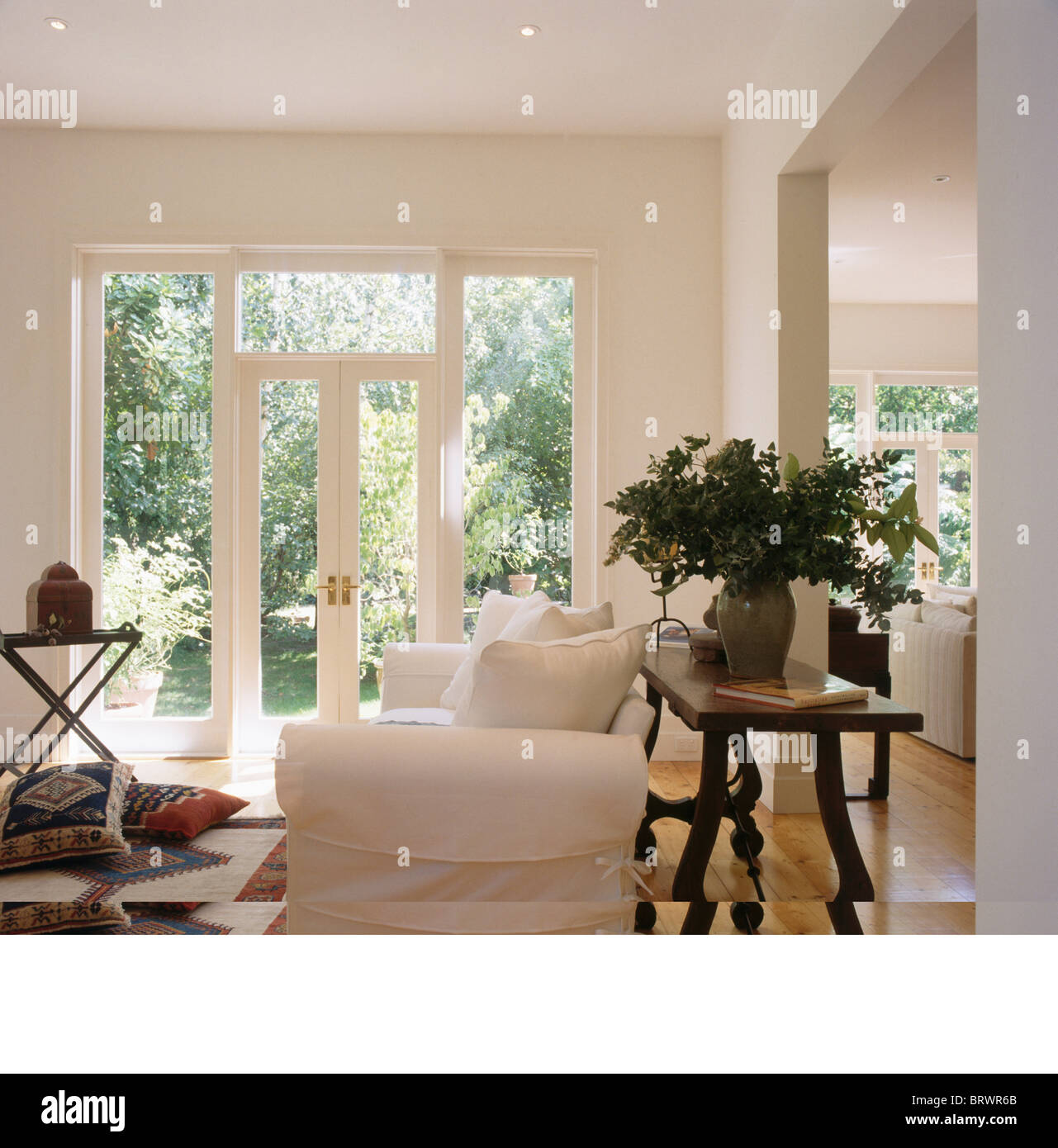 Stock Photo   Tall Vase Of Flowers On Antique Table Behind White Sofa In  Modern White Country Living Room Extension With French Windows Part 66