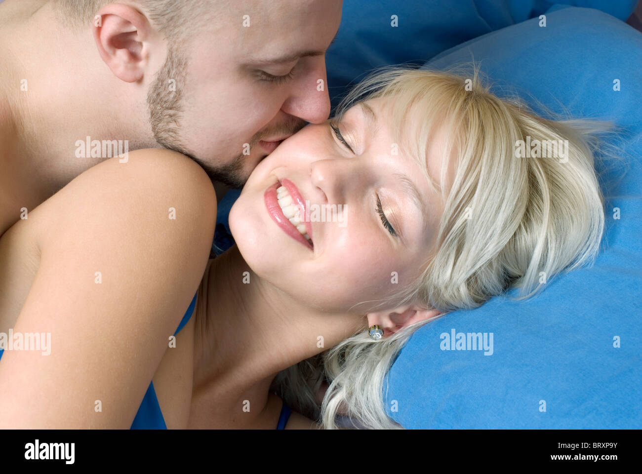 Close Up Of Young Man Kissing Woman In Bed