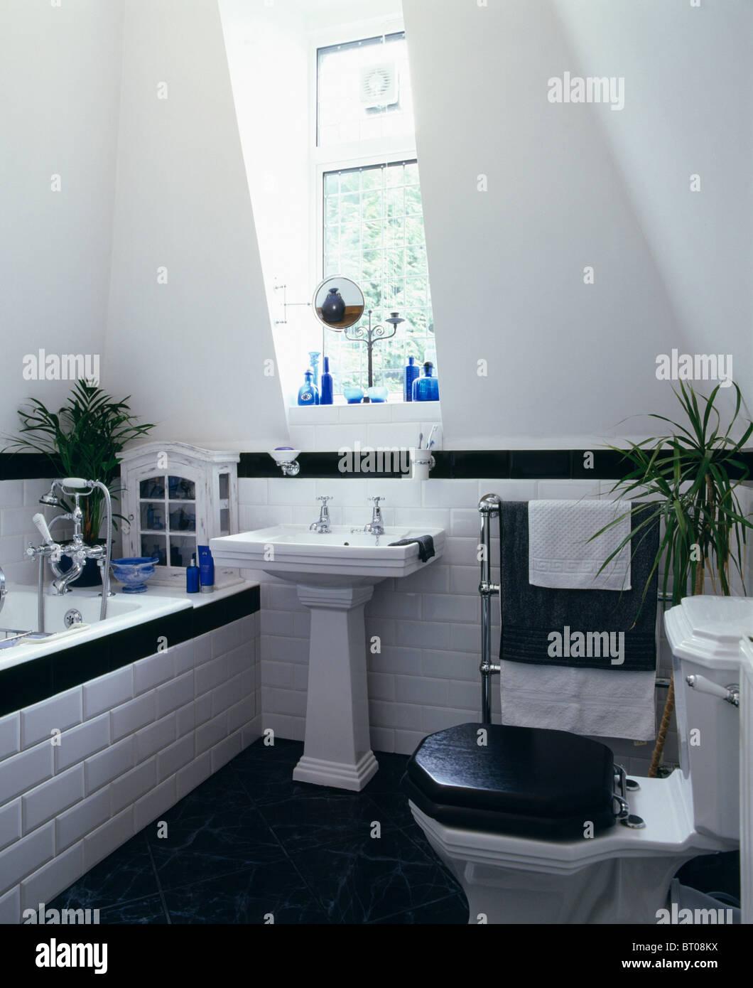 White Pedestal Basin Below Window In Blackwhite Attic Bathroom - White toilet with black seat