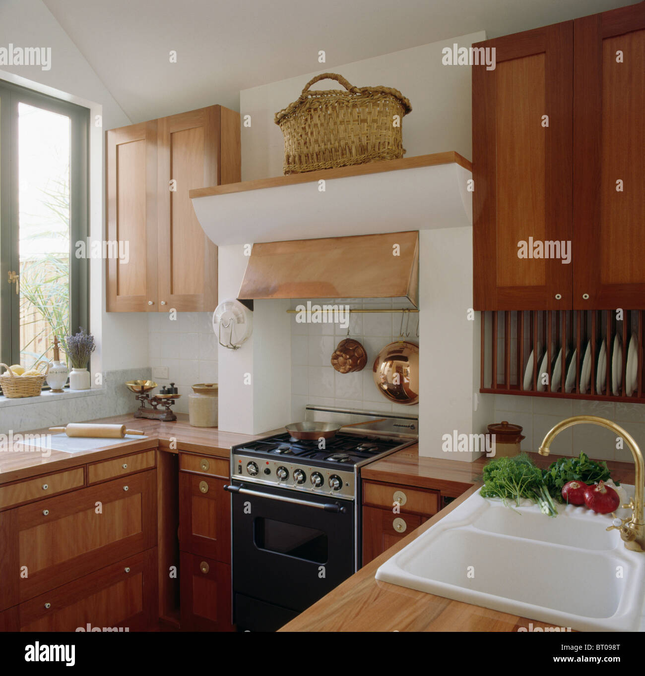Small Fitted Kitchen Basket On Shelf Above Black Oven In Small Kitchen With Pale Wood