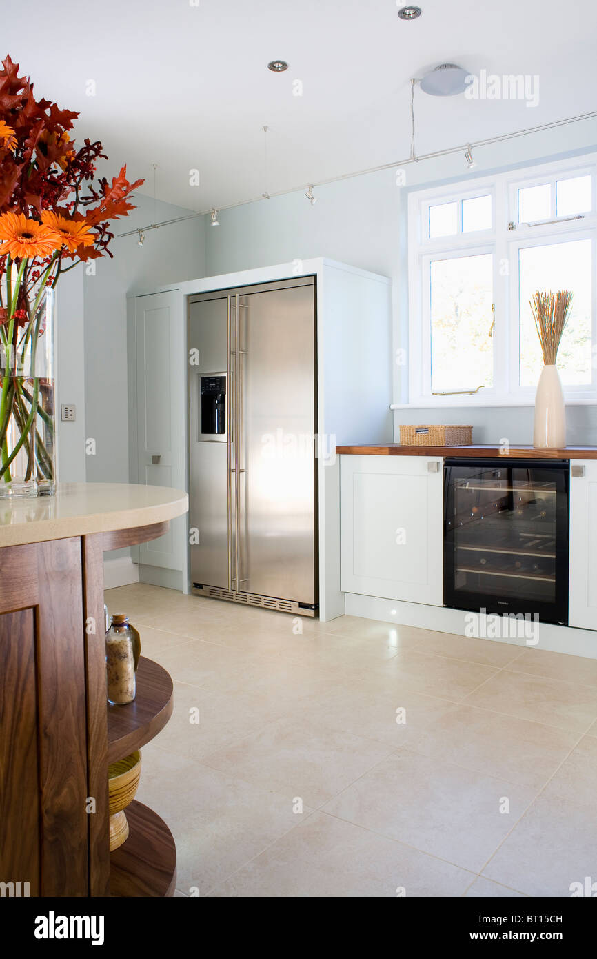 white fridge in kitchen. limestone flooring in modern white kitchen with large stainless-steel american-style fridge- fridge