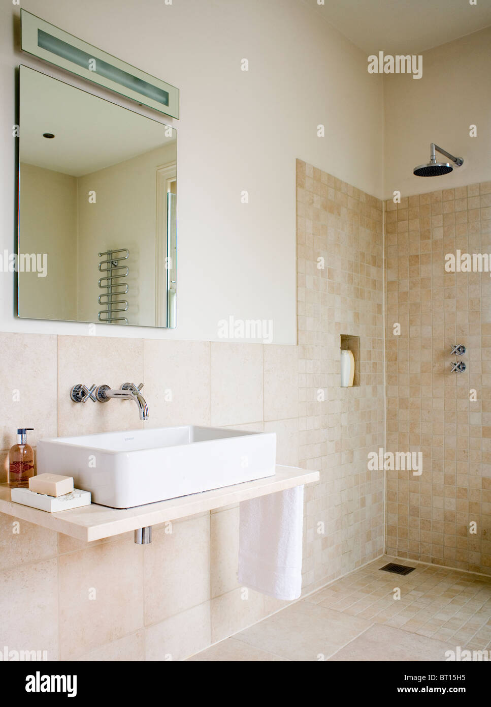 Mirror above rectangular white basin on vanity shelf in modern beige tiled  wet room with walk in shower. Mirror above rectangular white basin on vanity shelf in modern