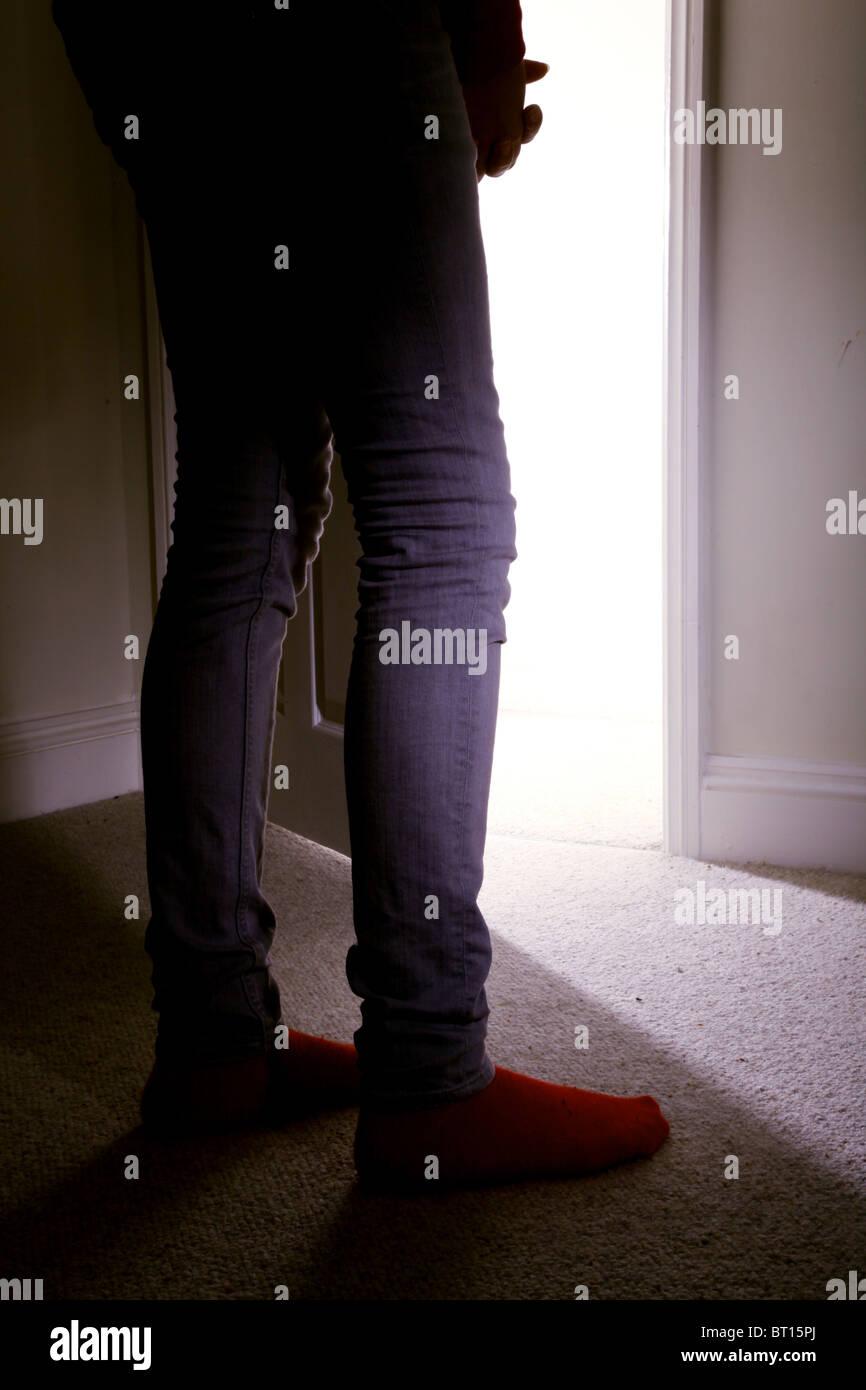 Young girl standing in a dark room facing an open door Stock Photo