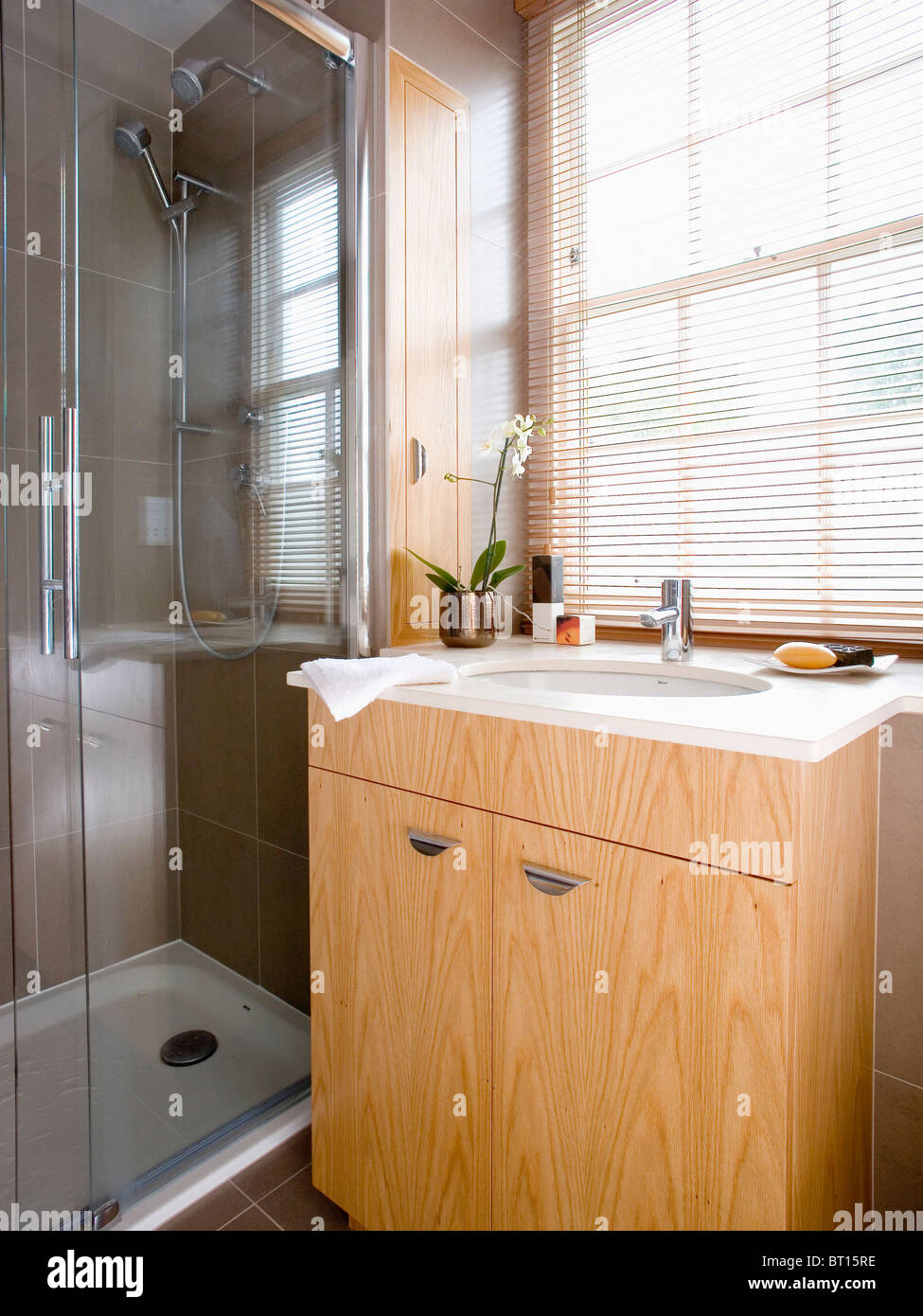 Bathroom Window Above Sink slatted blind on window above white basin in pale wood vanity unit