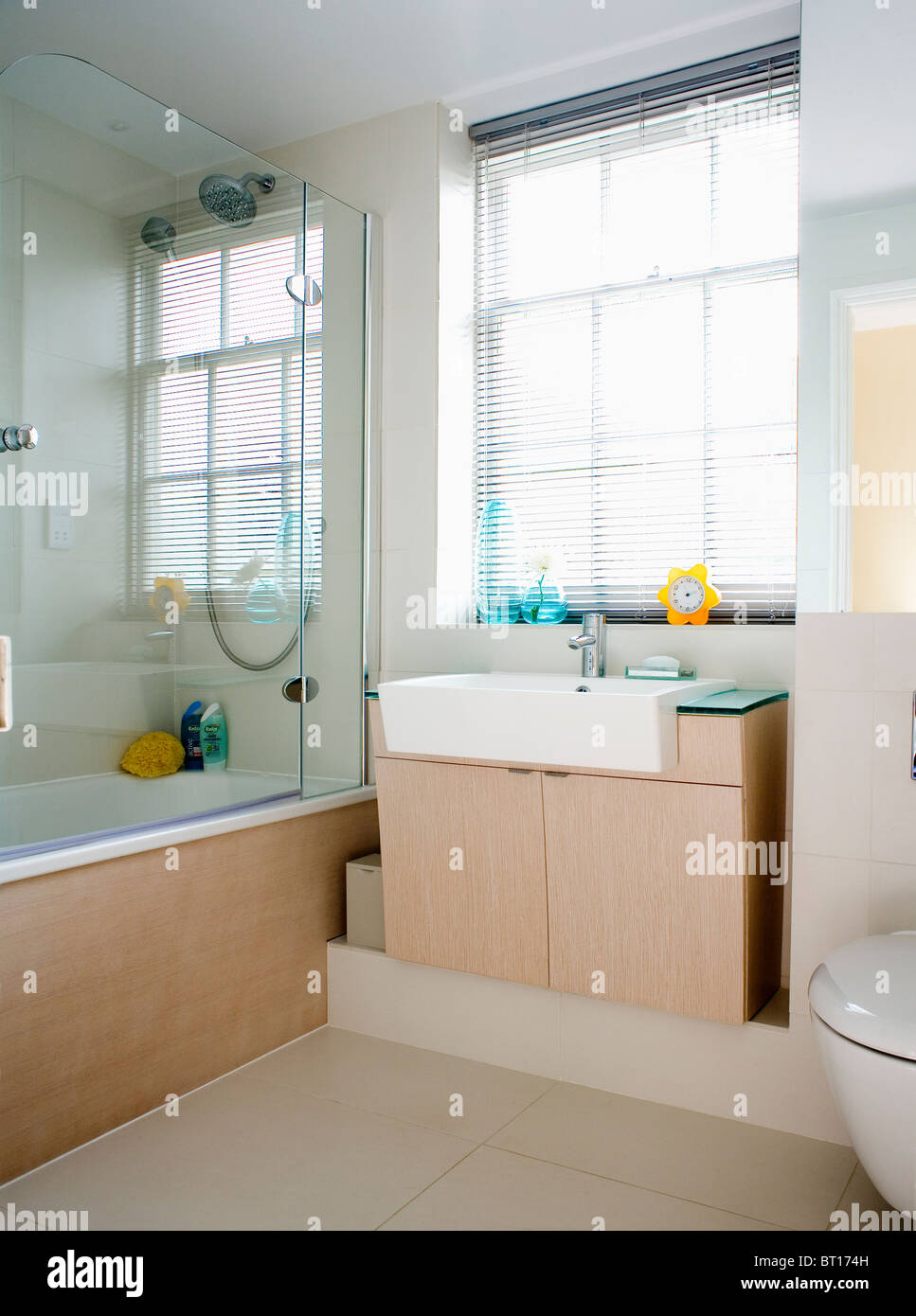 Glass shower screen on bath in modern white bathroom with white basin  on pale wood vanity. Glass Shower Screen On Bath In Modern Spanish Bathroom With Voile