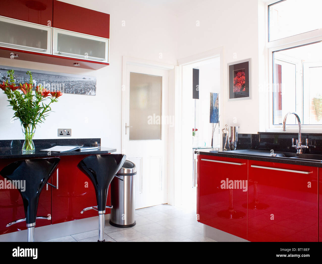 fitted units with red acrylic doors and black granite