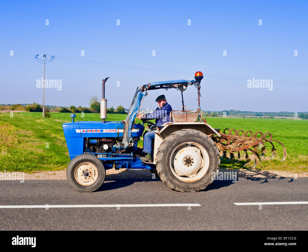 Old ford 2000 super tractor driven along country road france stock image