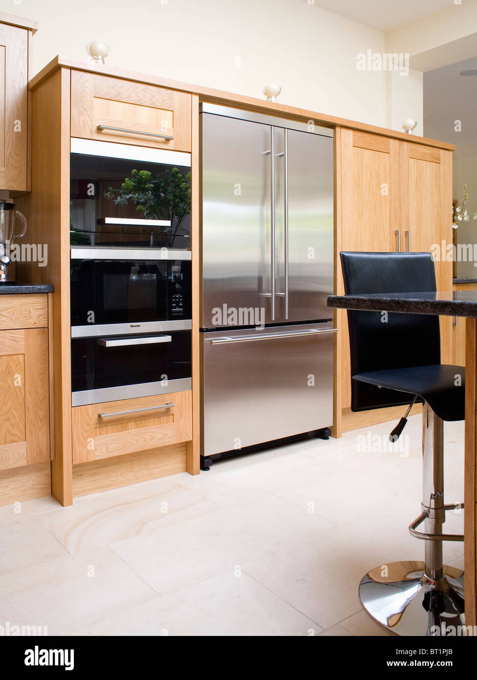 Limestone Flooring In Kitchen Large Stainless Steel Refrigerator And Double Ovens In Fitted Unit
