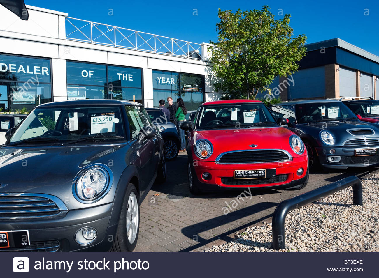 Mini used cars on a garage forecourt in cheltenham uk people talking to salesman