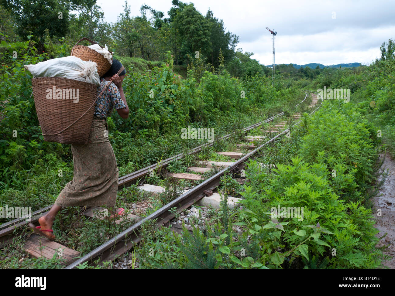 woman carrying heavy load in back basket on train track ...