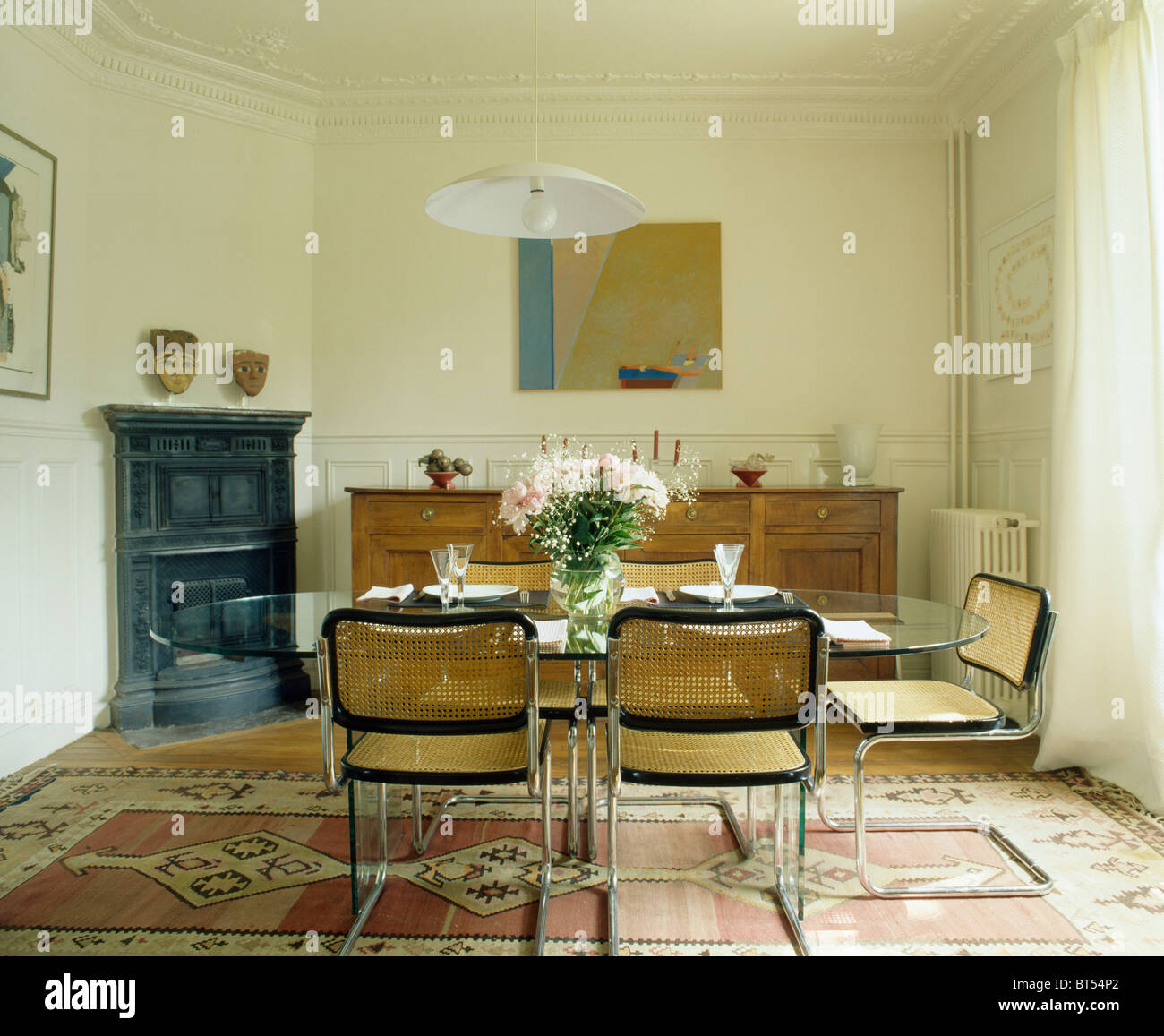 modern chrome cane chairs in french townhouse dining room with modern chrome cane chairs in french townhouse dining room with patterned oriental rug on floor and corner fireplace