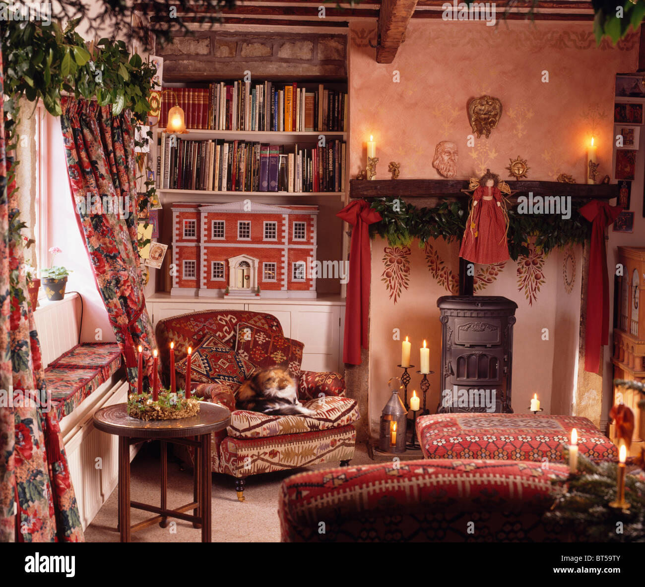 Lighted candles fireplace with wood-burning stove in ...