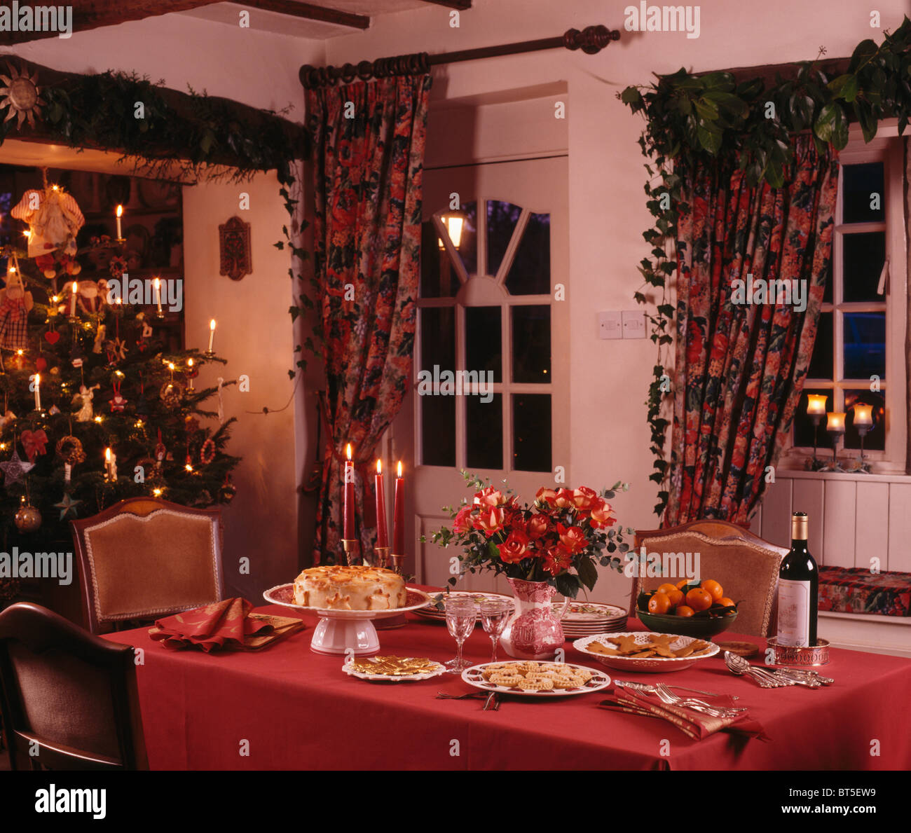 red cloth on table set for christmas tea in cottage dining room red cloth on table set for christmas tea in cottage dining room with christmas tree in the corner of the room