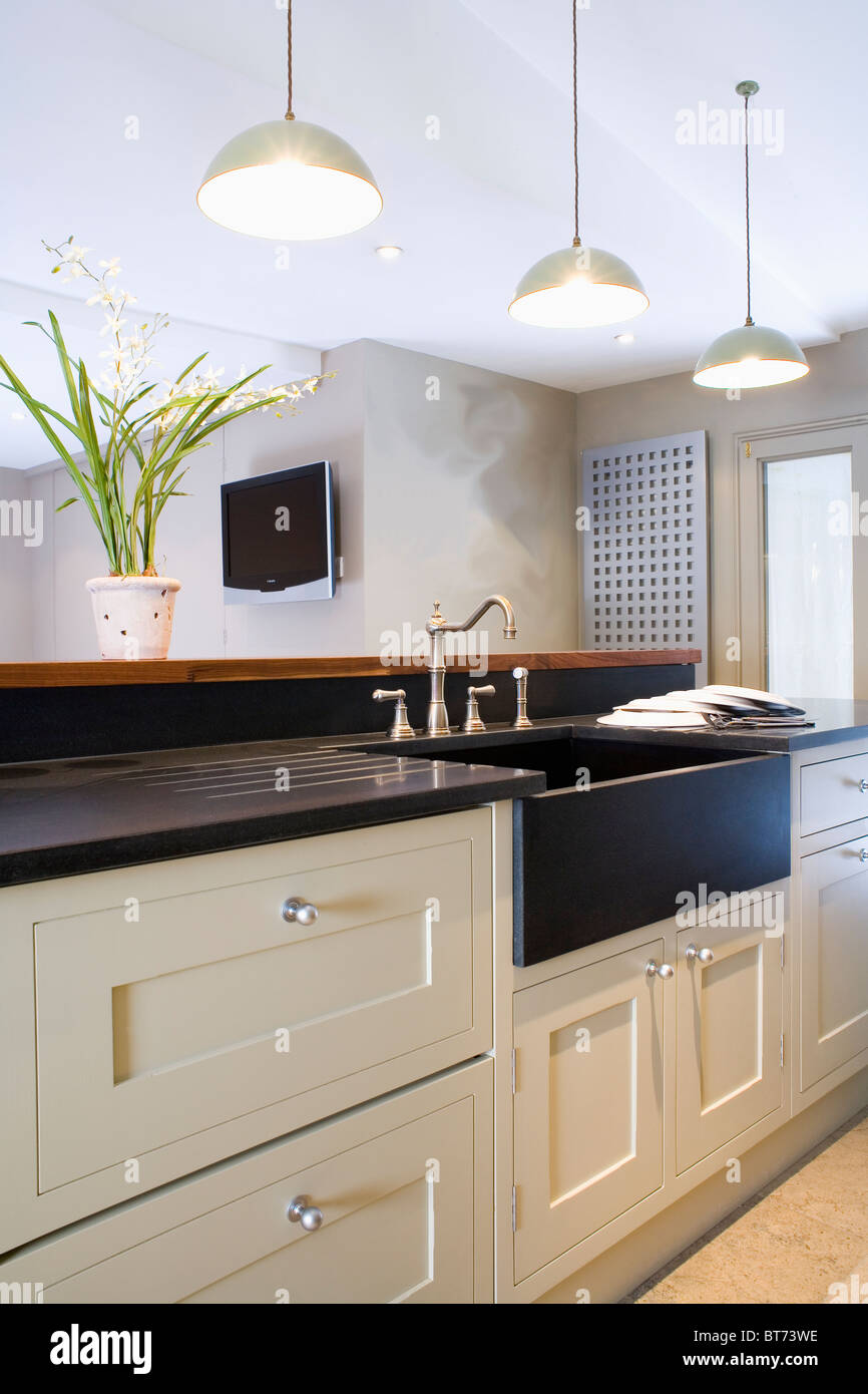 White Pendant Lights Above Black Sink In Cream Fitted Island Unit Stock Photo