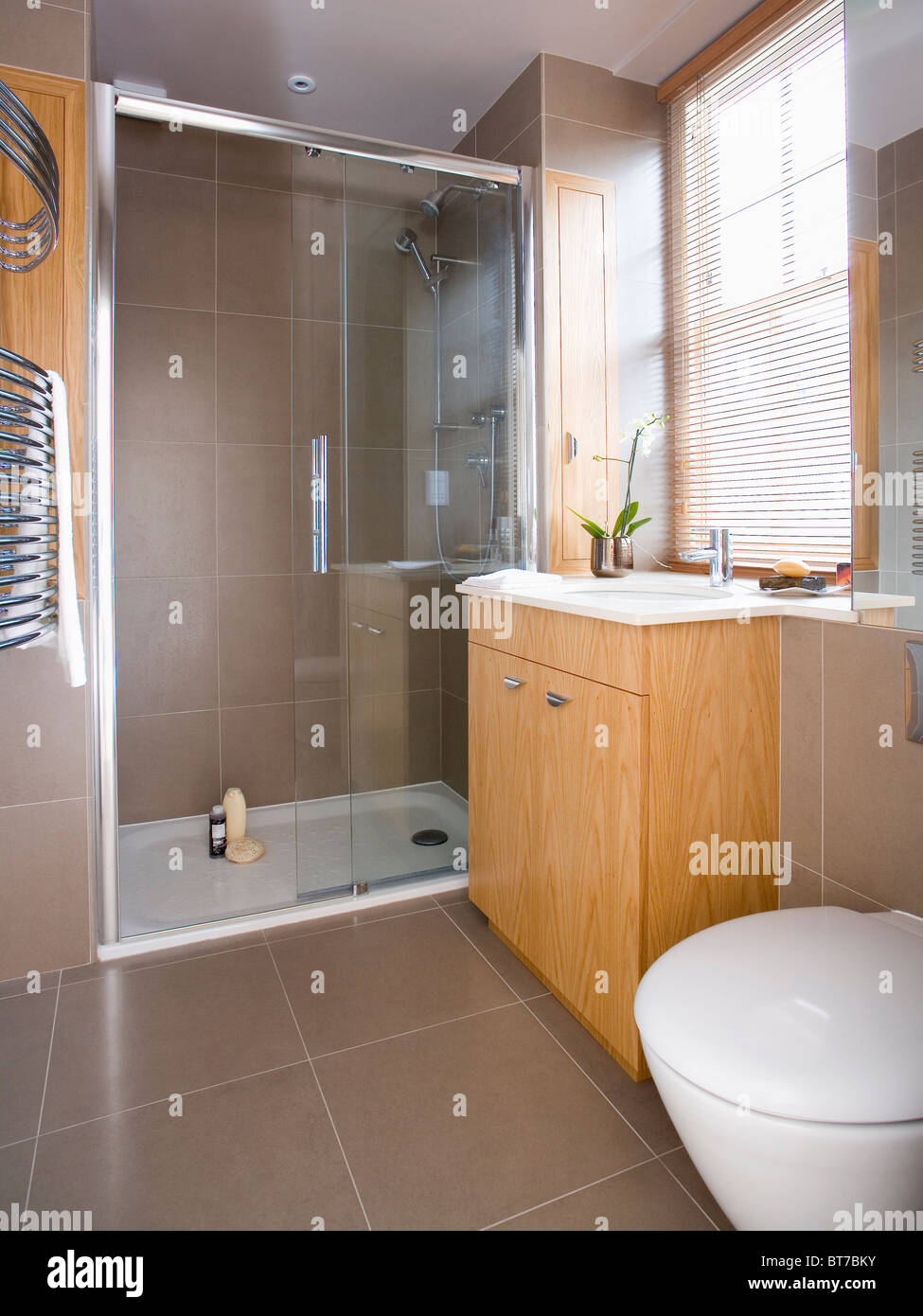 Glass Doors On Large Walk In Shower In Modern Bathroom With Beige Tiled  Floor And Slatted Wooden Blind