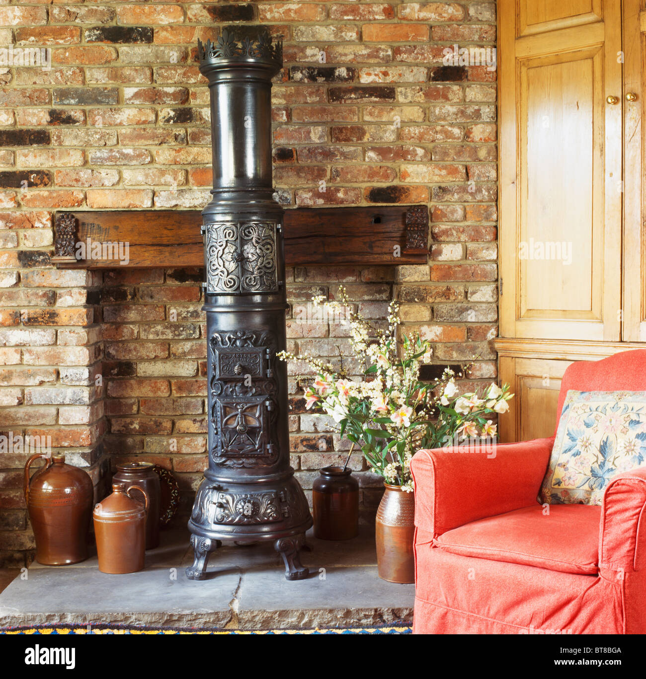 black cast-iron victorian-style stove in brick fireplace of