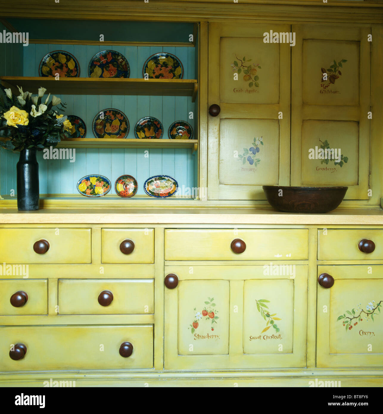 floral painted doors on pale yellow fitted cupboards in cottage