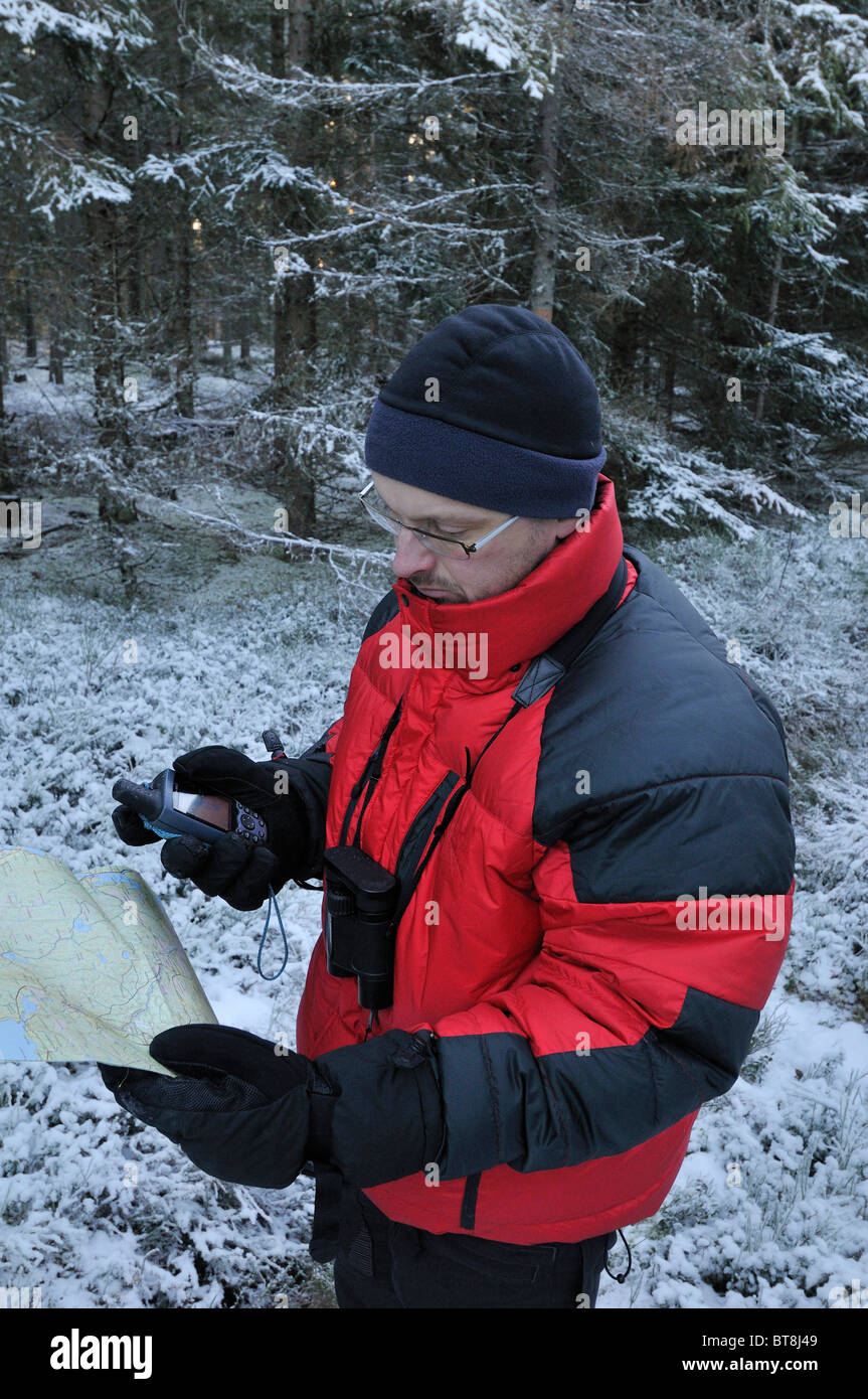 Hiker Verifying The Course With A Map And A GPS Receiver Near - Sweden map gps