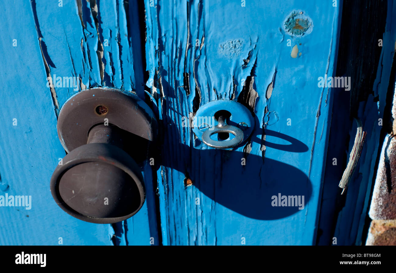 door knob and key in a wooden door hole stock photo royalty free