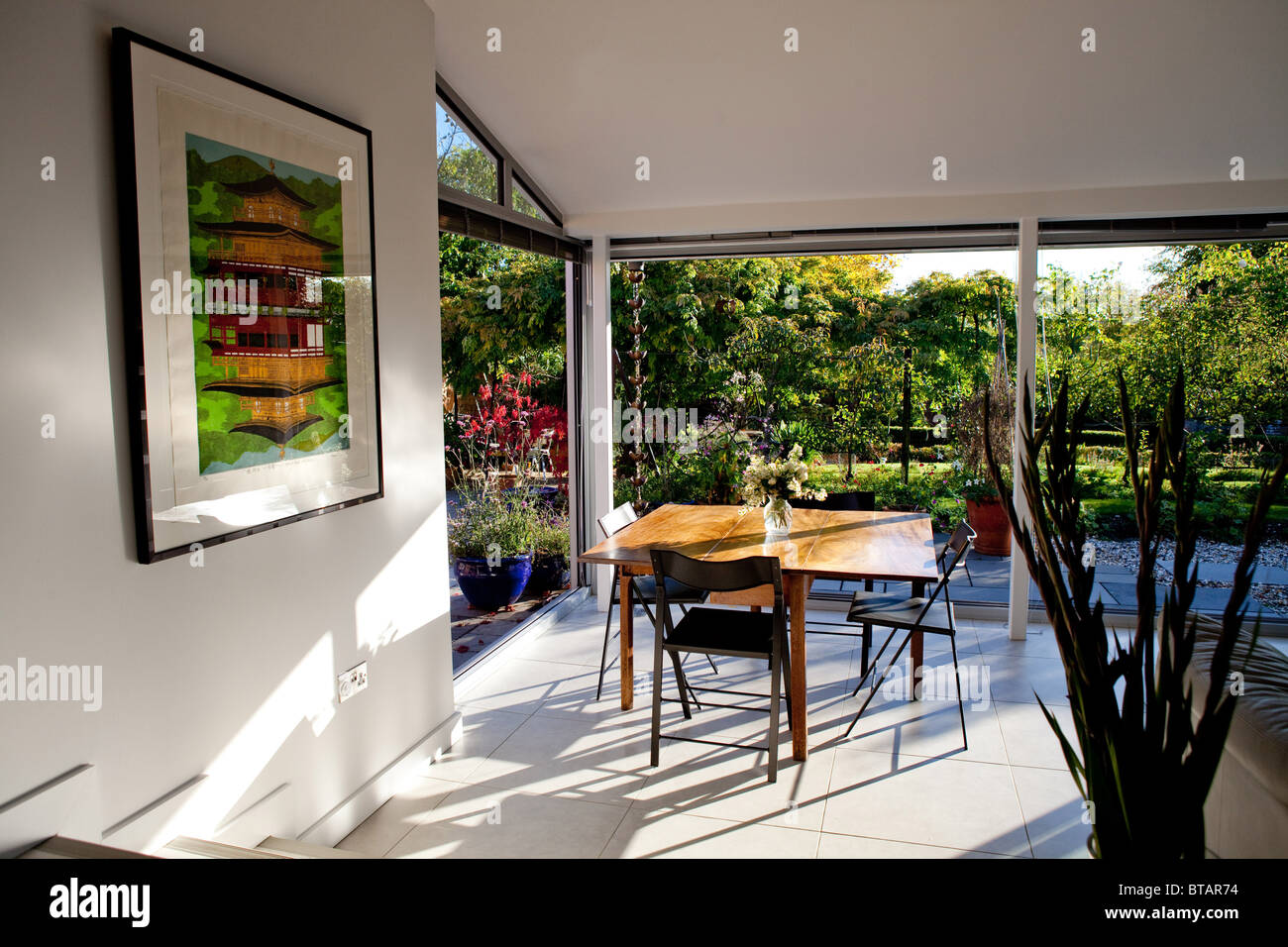 A Dining Room With Doors That Open Onto A Patio And Garden
