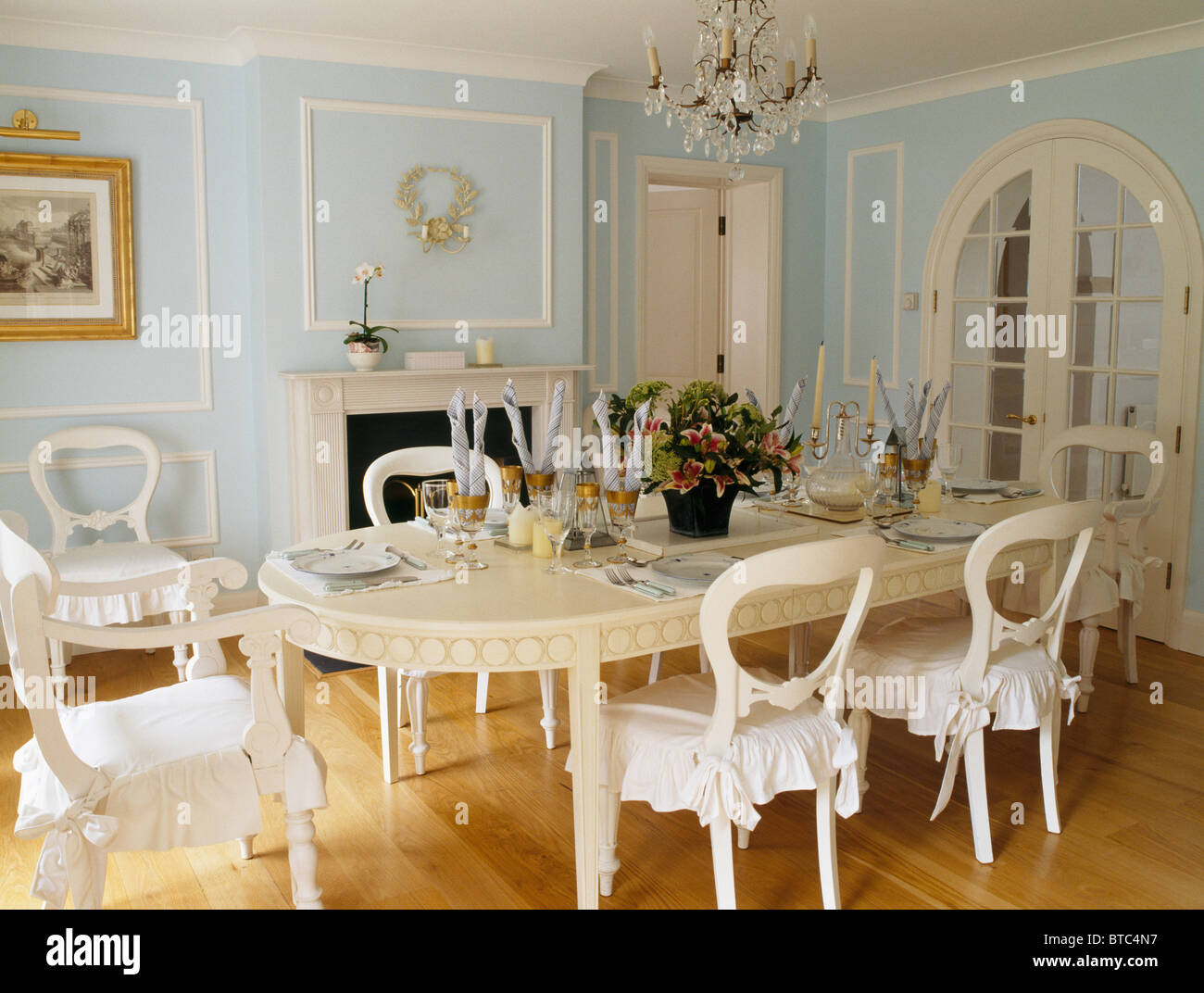 Long cream oval table and cream chairs with white cushions in pale ...