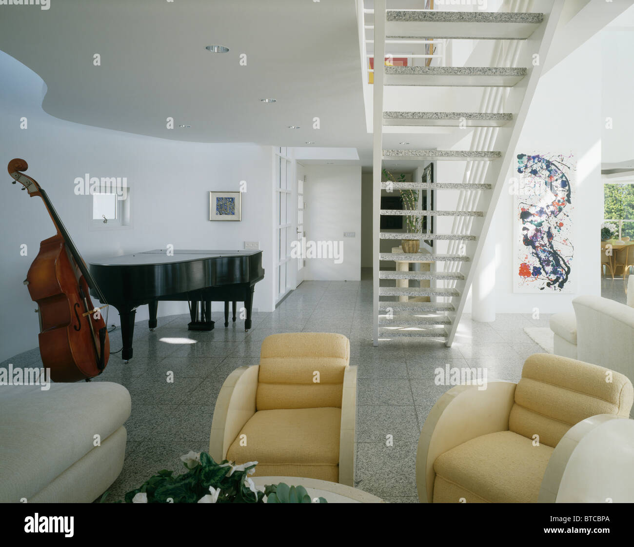Captivating Grand Piano And Bass Viol In Large Modern Living Room With Art Deco Style  Armchairs Below Open Tread Staircase