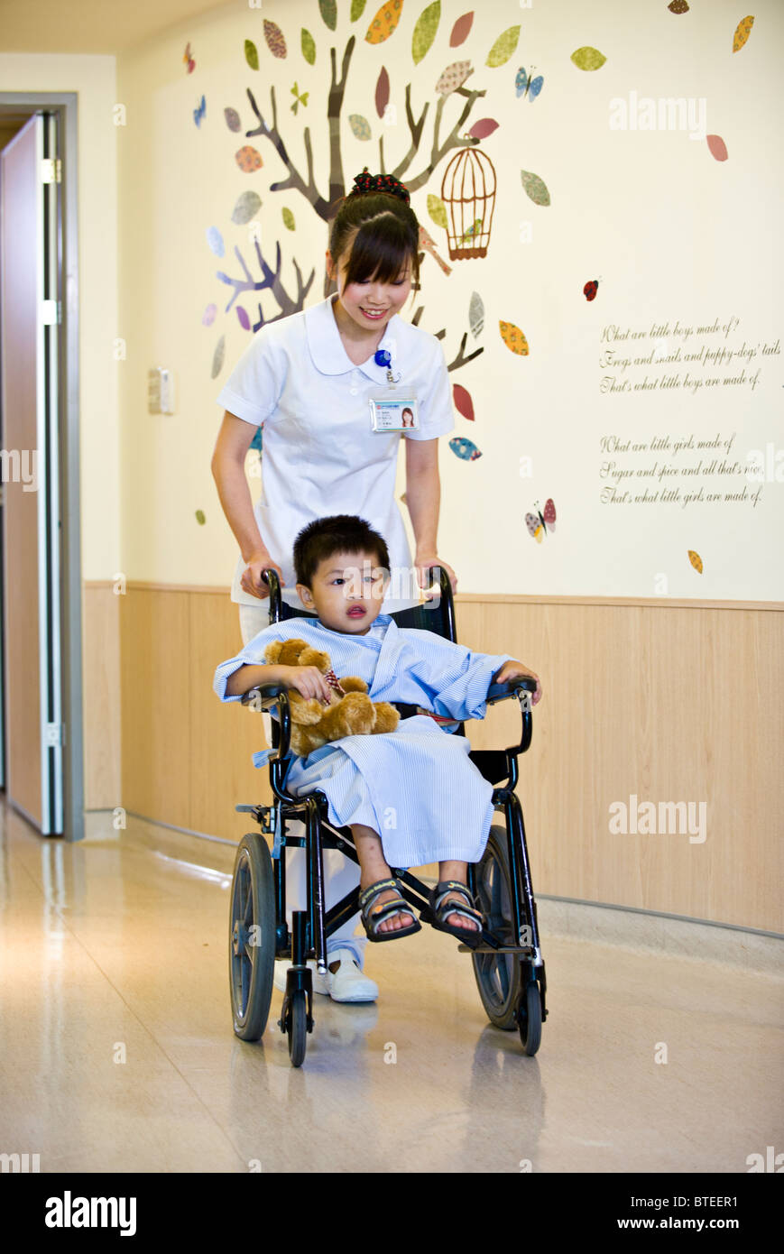 Person Pushing Wheelchair - Nurse pushing young child patient in wheelchair down corridor in hospital pediatrics unit stock image