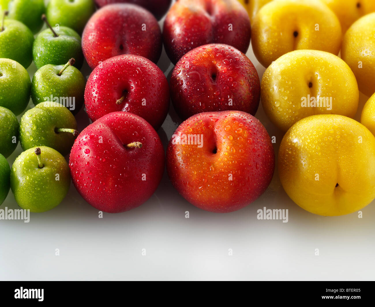 mixed red yellow and green plums against a white