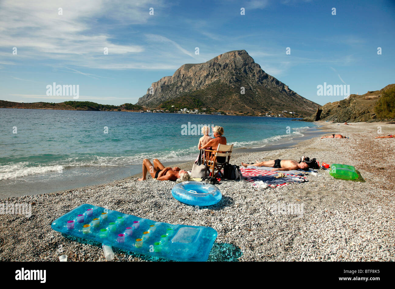 People Sunbathing At Myrties Beach With Telendos Island In ...