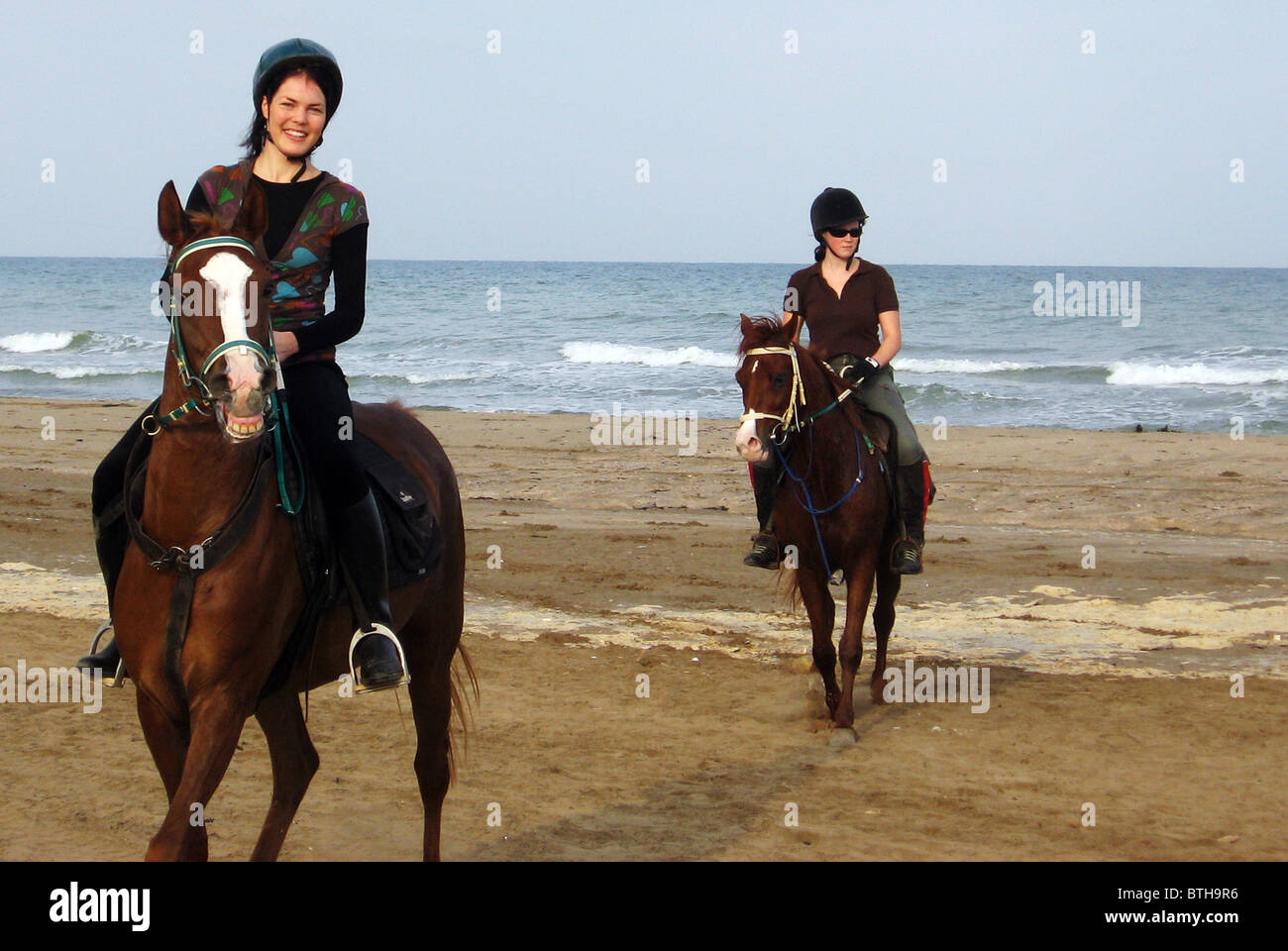 Young women ride horses on the beach in oman in the middle east young women ride horses on the beach in oman in the middle east sciox Choice Image