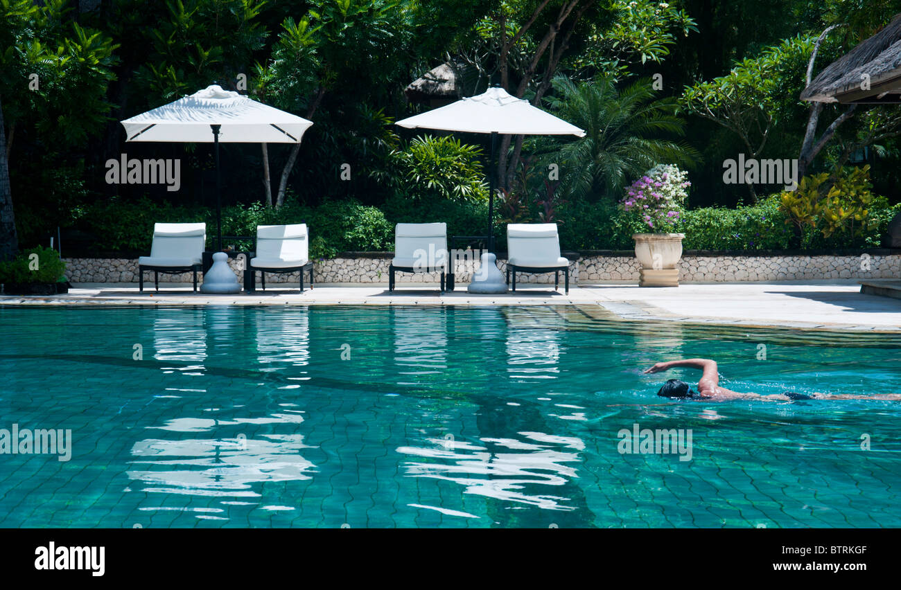 Stock photo swimming pool at the melia bali hotel nusa dua bali indonesia with one person swimming