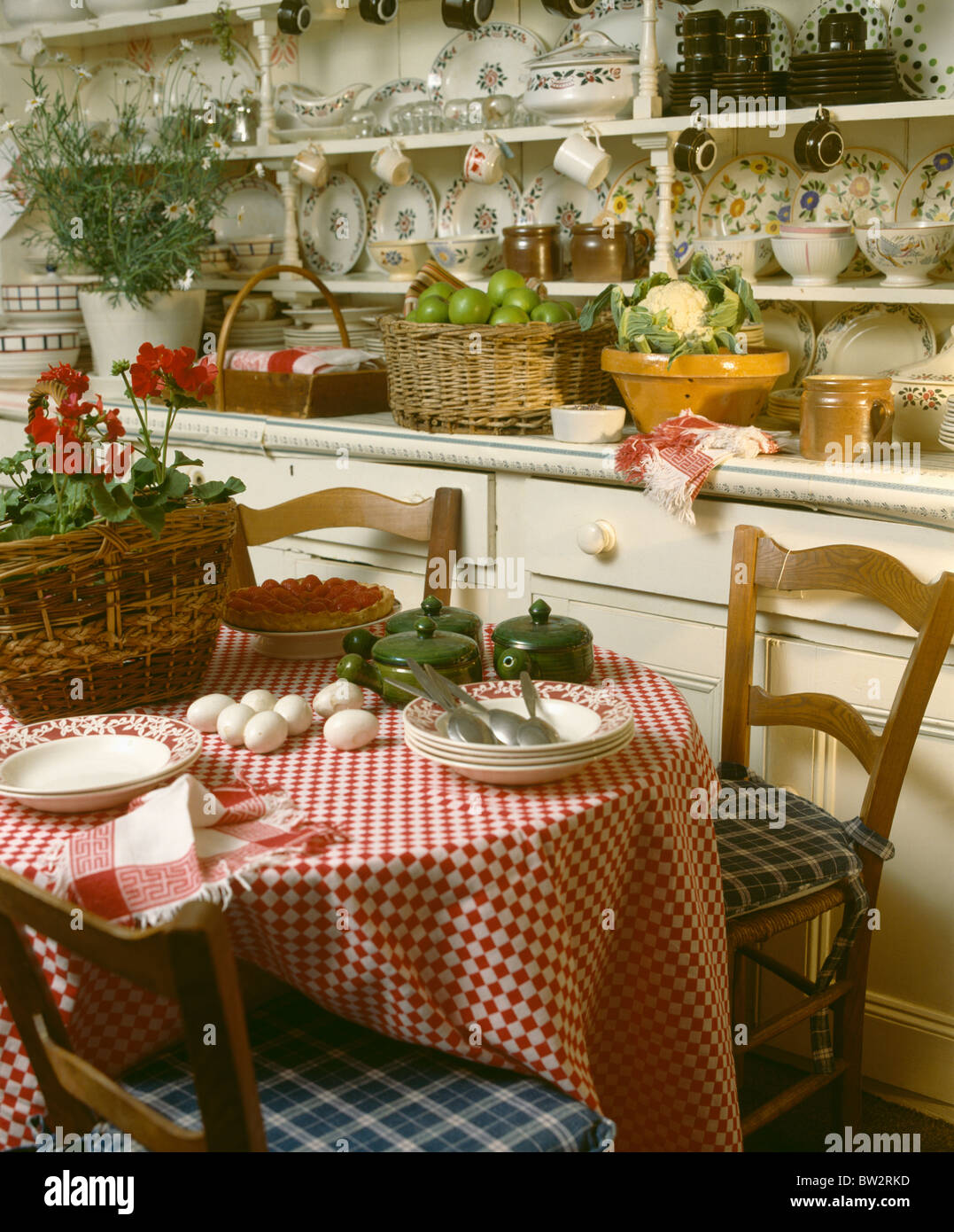 Red Checked Cloth On Circular Table In Cottage Kitchen Dining Room With Crockery Large Dresser